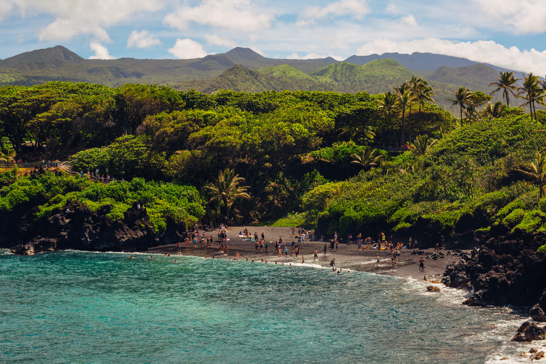 La playa de Honokalani, considerada sagrada por el pueblo hawaiano, es una pequeña media luna volcánica escondida dentro del hermoso parque estatal Waianapanapa en Hawai. Su arena negra como el azabache, el agua turquesa brillante y el frondoso bosque verde se combinan para crear una de las maravillas naturales más impresionantes del mundo