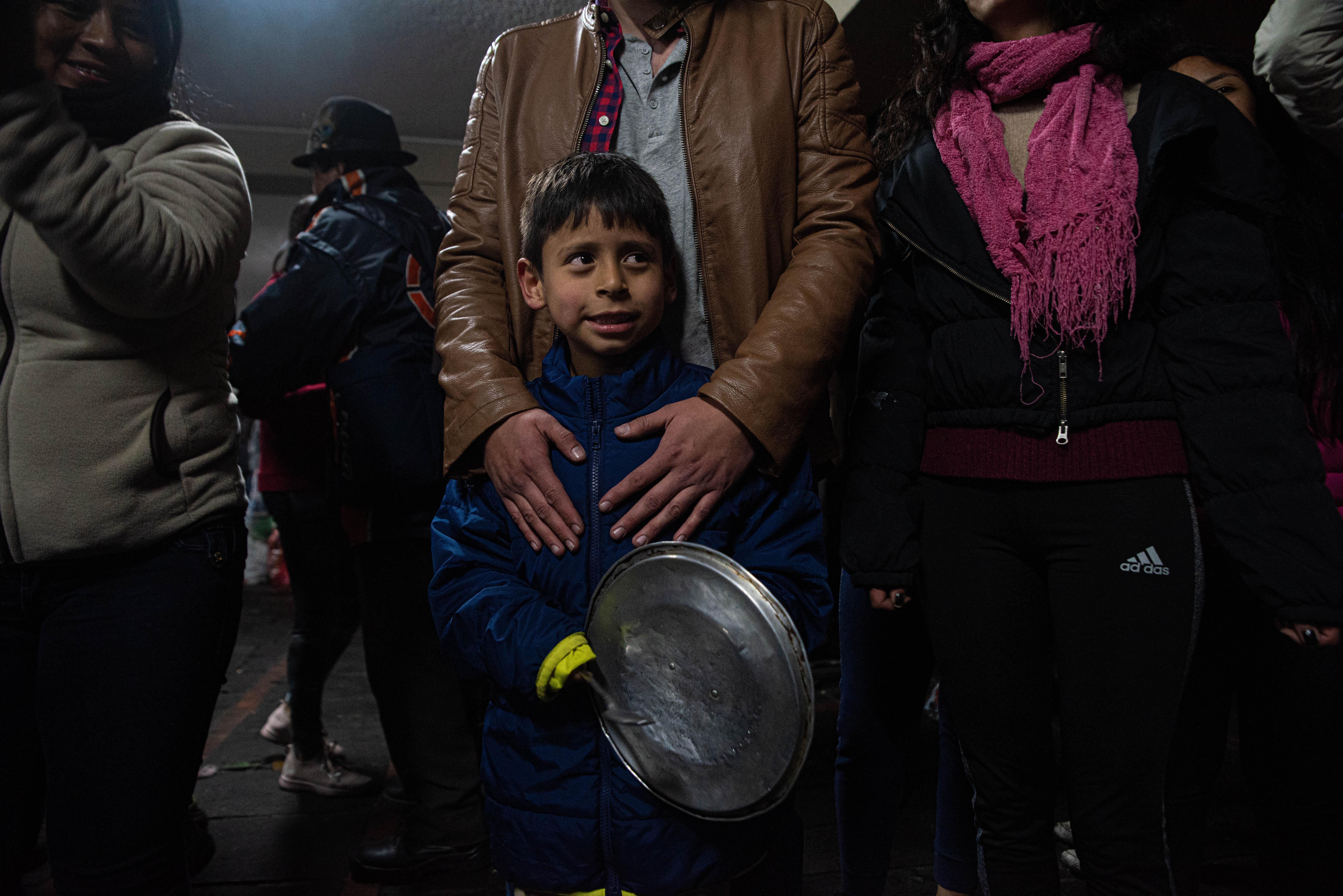 Un niño con su padre golpea la tapa de una cacerola para celebrar durante festejos que se vivieron en Quito en la noche del domingo