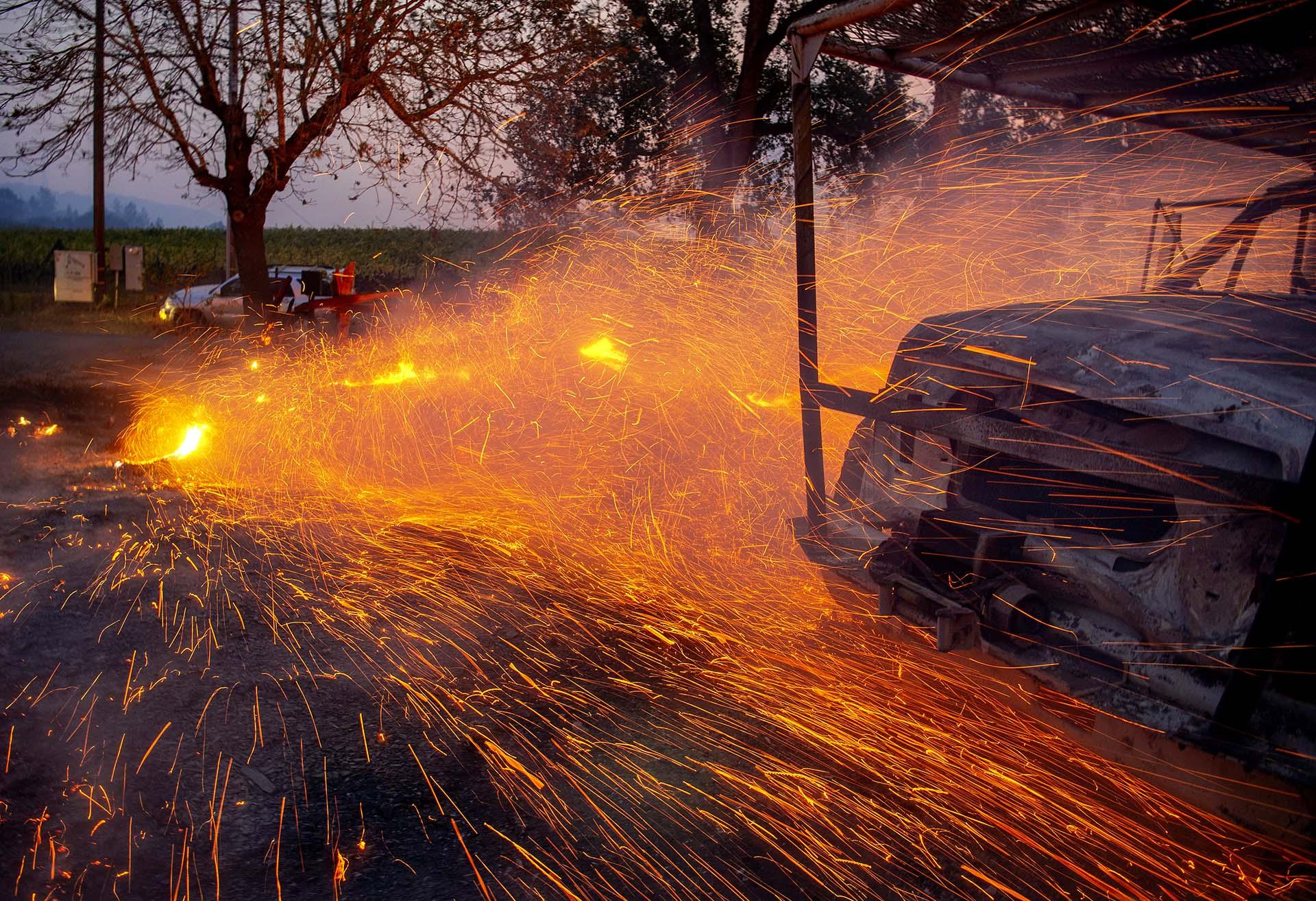 El fuego y las brasas soplan alrededor de un camión utilitario quemado durante el incendio de Kincade en Healdsburg, California, el 27 de octubre de 2019