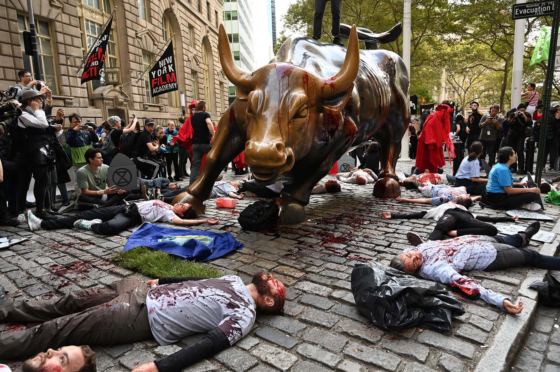 Los manifestantes cubiertos de sangre falsa se reúnen alrededor del Wall Street Bull durante una manifestación de
