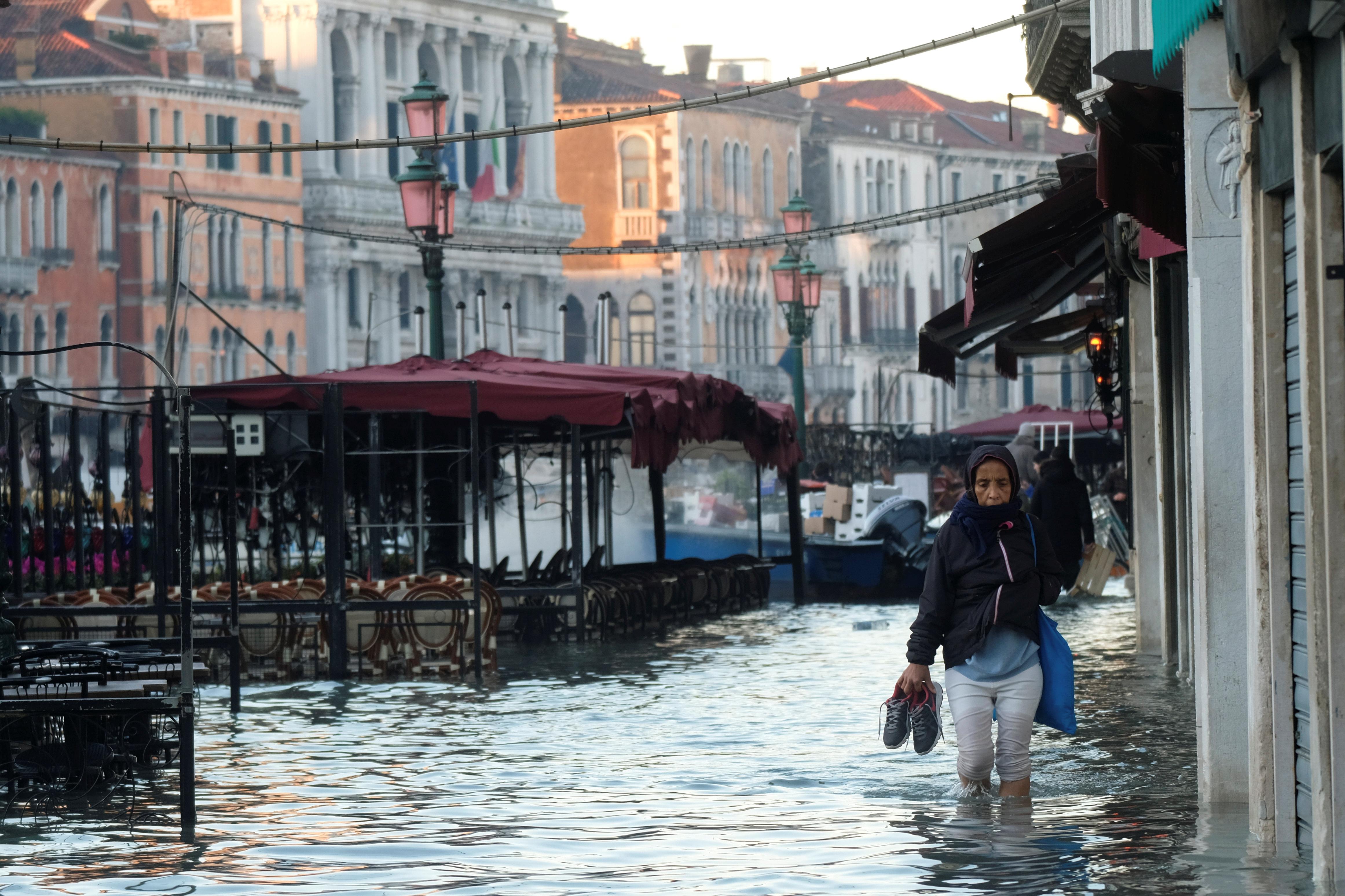 Una mujer camina por una calle inundada (REUTERS/Manuel Silvestri)