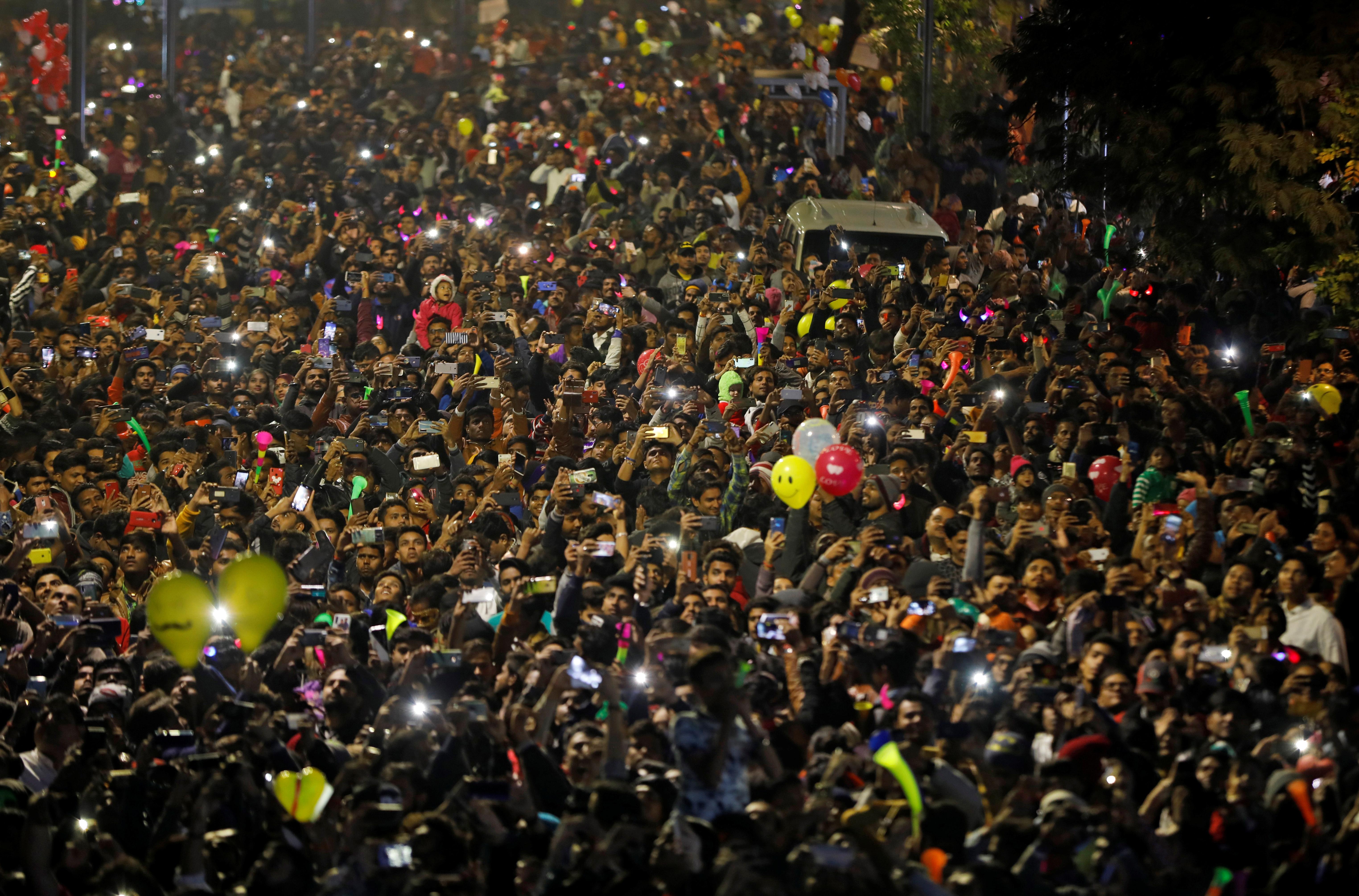 La gente enciende sus teléfonos móviles mientras celebra la cuenta atrás del Año Nuevo en una carretera de Ahmedabad, India (REUTERS/Amit Dave)