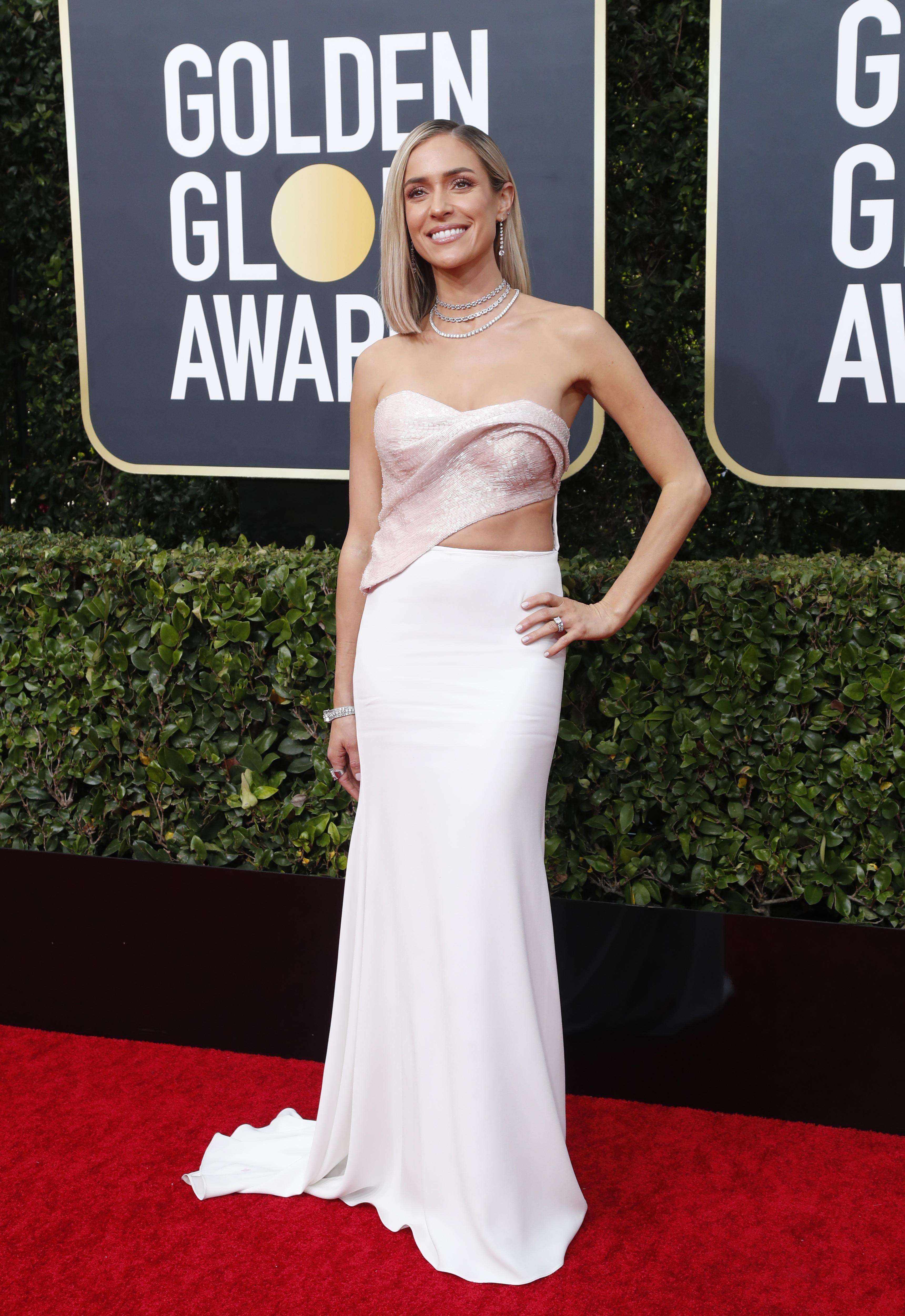 Kristin Cavallari apostó por un conjunto de dos piezas. Un corse rosa metalizado y una falda sirena blanca. Completó su look con delicadas gargantillas de cristales, brazaletes y anillos