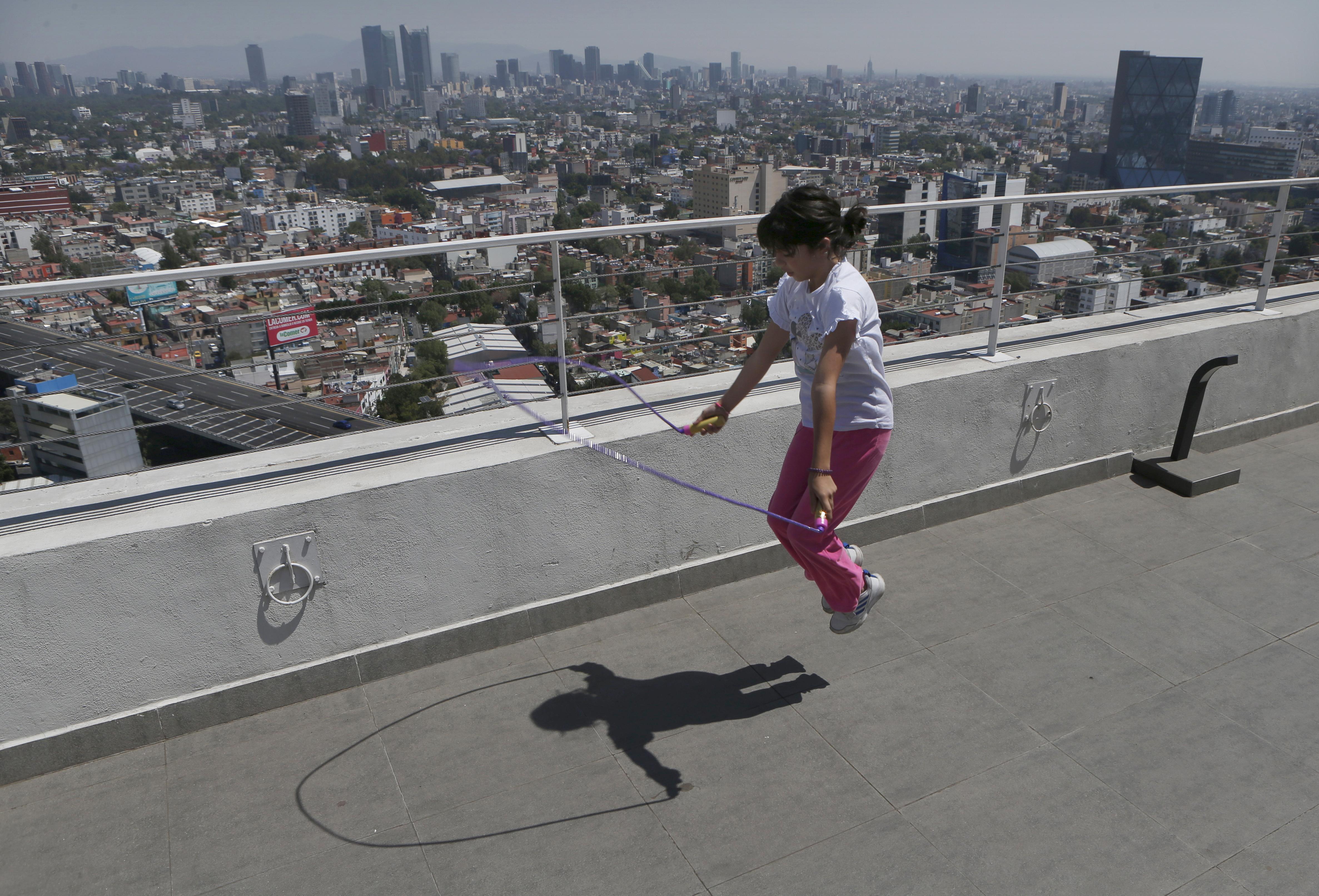 Una niña se queda en casa después de que su escuela canceló las clases debido a la propagación del nuevo coronavirus, Sofía Cortés salta a la cuerda en el techo de un edificio en la Ciudad de México, el martes 31 de marzo de 2020.