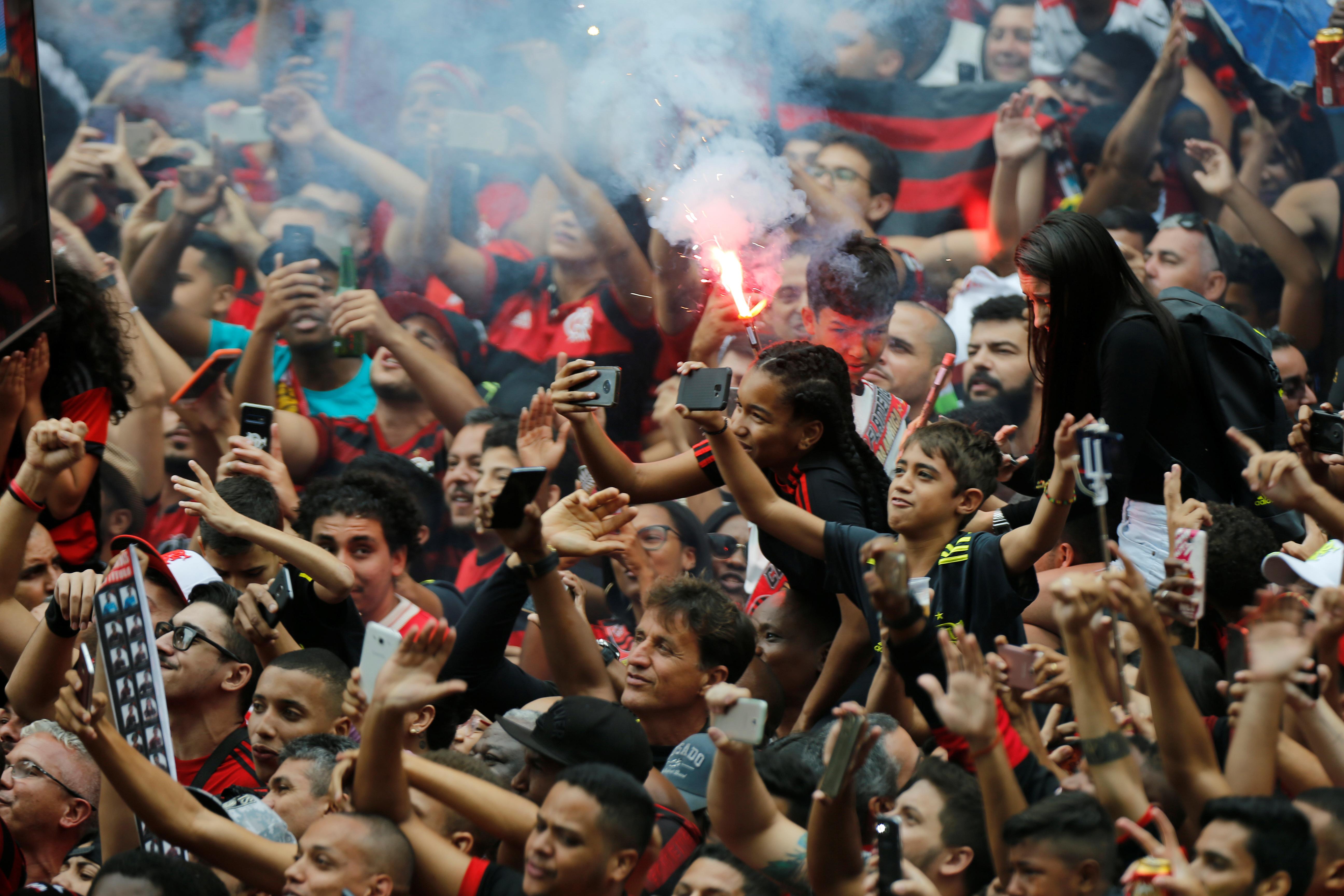Los hinchas desplegaron banderas y lanzaron fuegos artificiales mientras los campeones de la Copa Libertadores recorrían las calles de la ciudad en un autobús descapotable