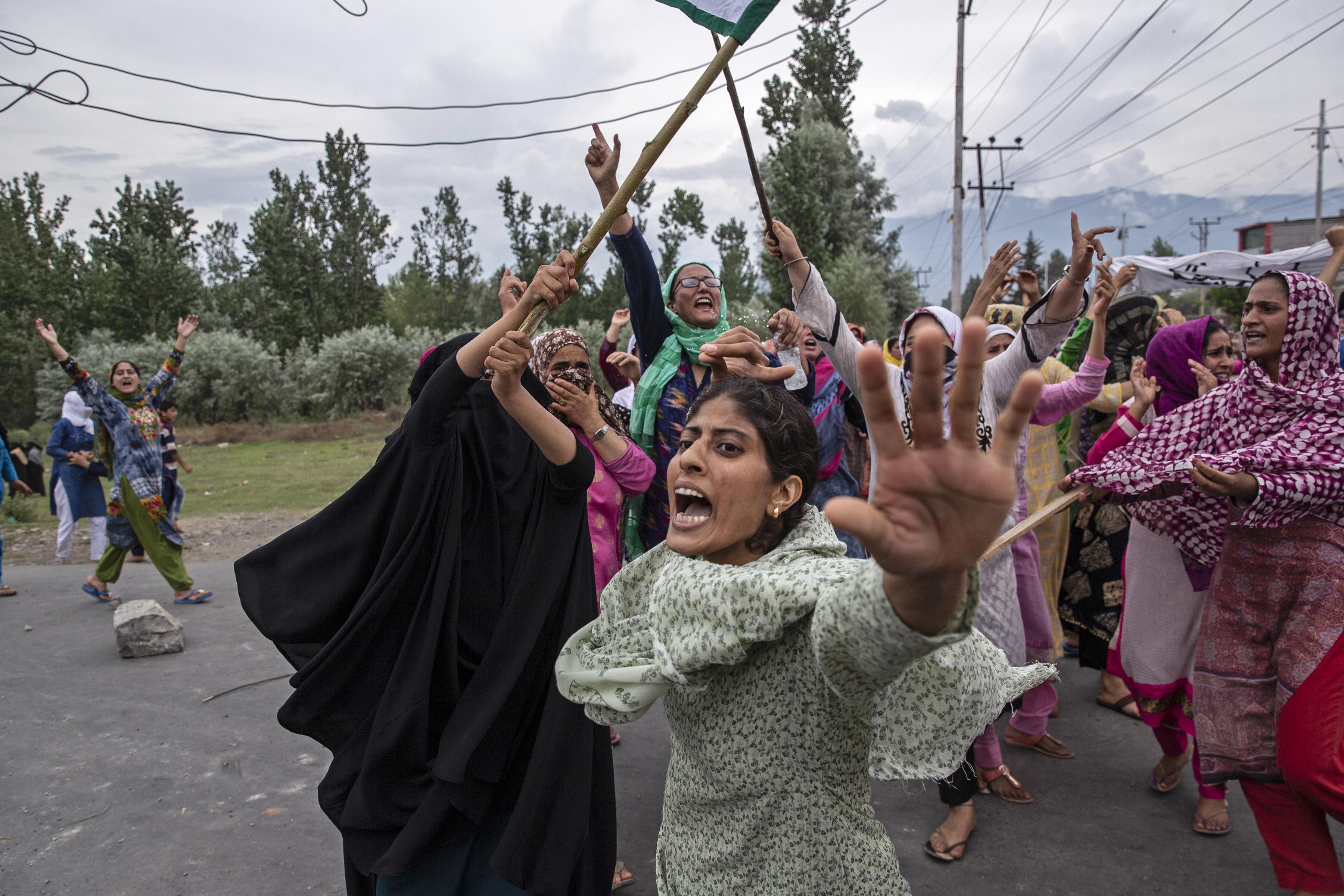 Las mujeres gritan consignas mientras los policías indios disparan gases lacrimógenos y municiones en el aire para detener una marcha de protesta en Srinagar (Foto AP / Dar Yasin)