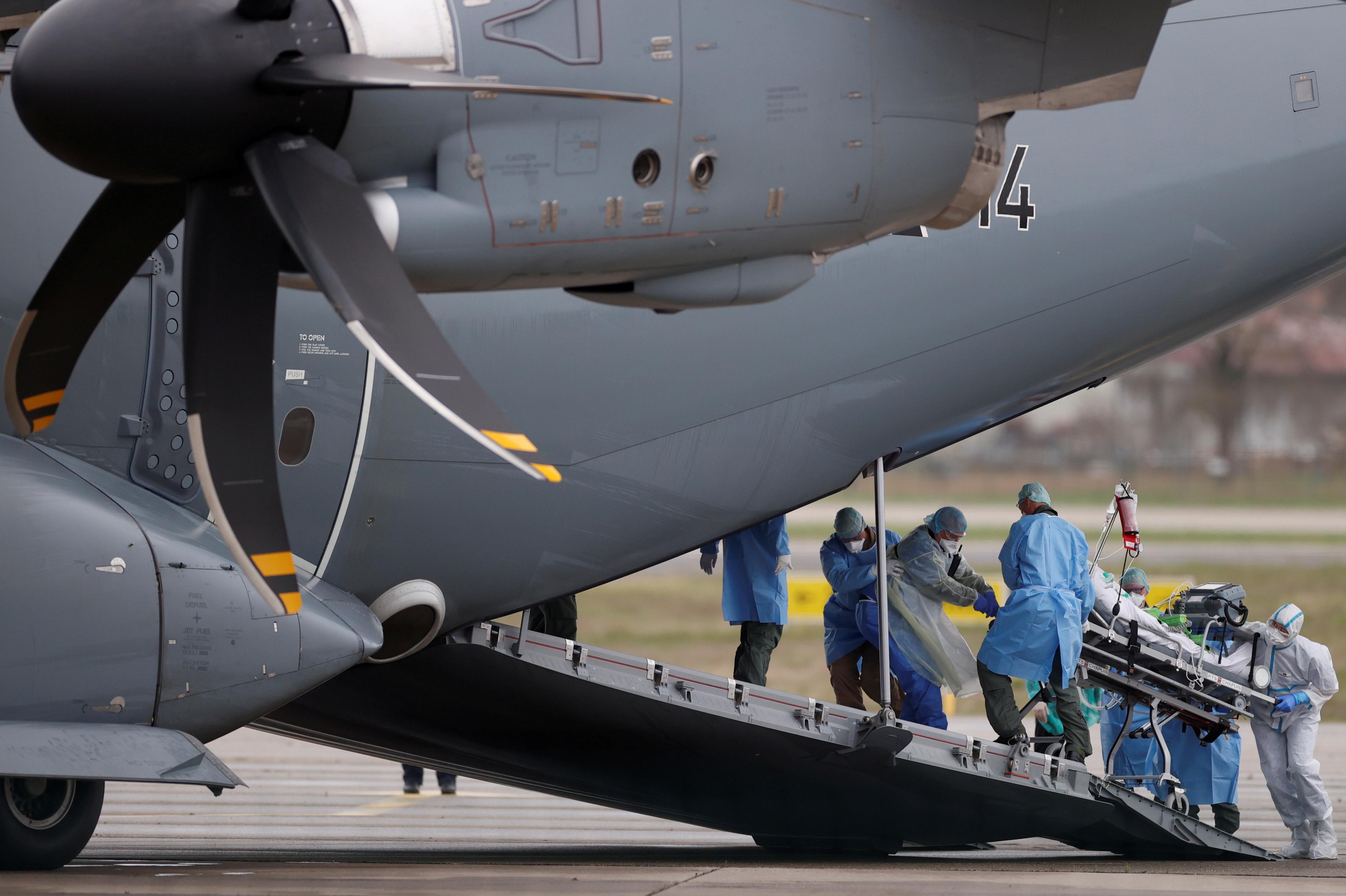 Un paciente es llevado en camilla a un avión militar alemán durante una operación de traslado (REUTERS/Christian Hartmann)