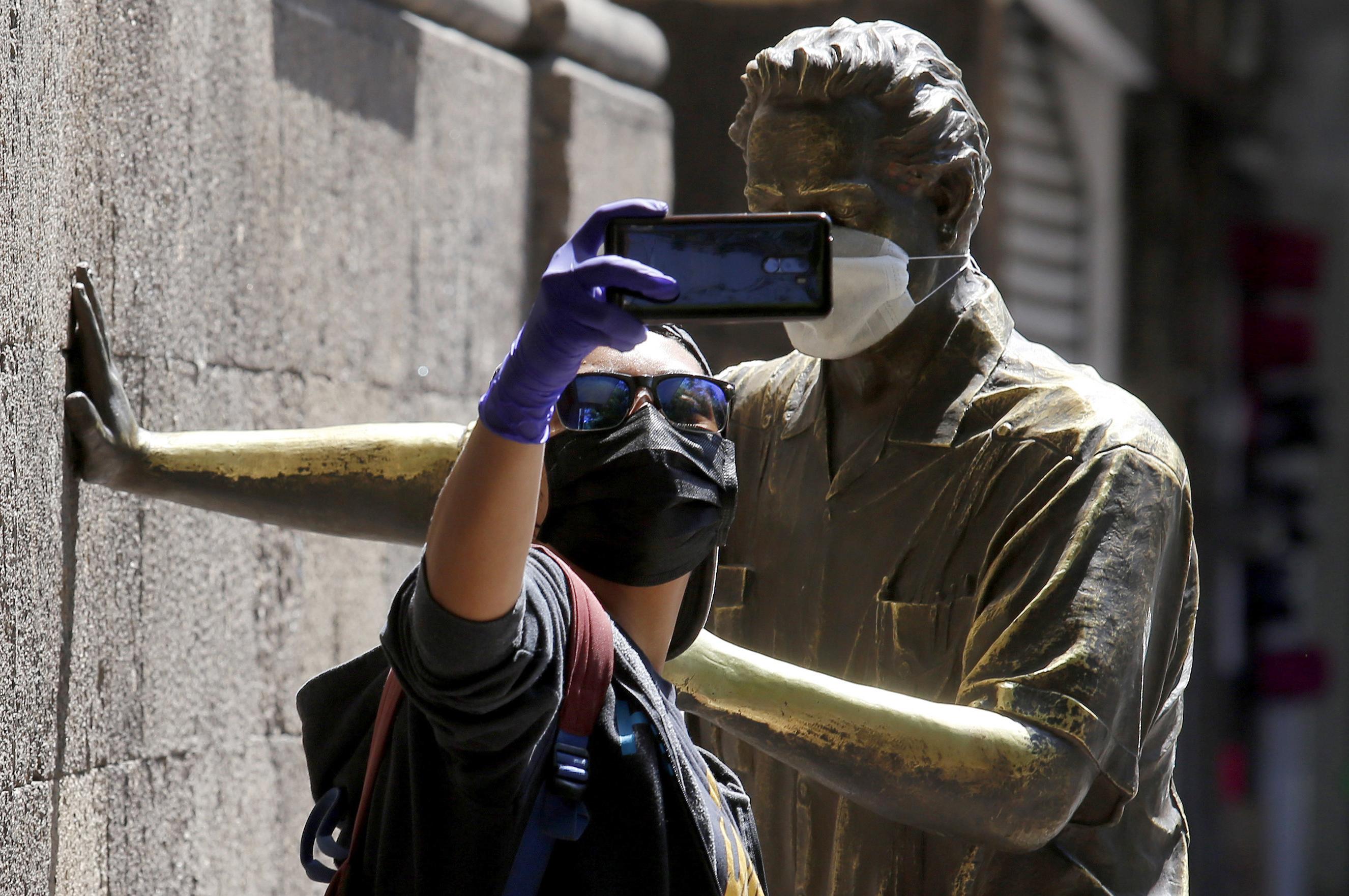 Un hombre se toma una selfie frente a una estatua del ingeniero mexicano Jorge Matute (1912-2002) con una máscara facial, durante la nueva pandemia de coronavirus COVID-19, en Guadalajara, México, el 31 de marzo de 2020.