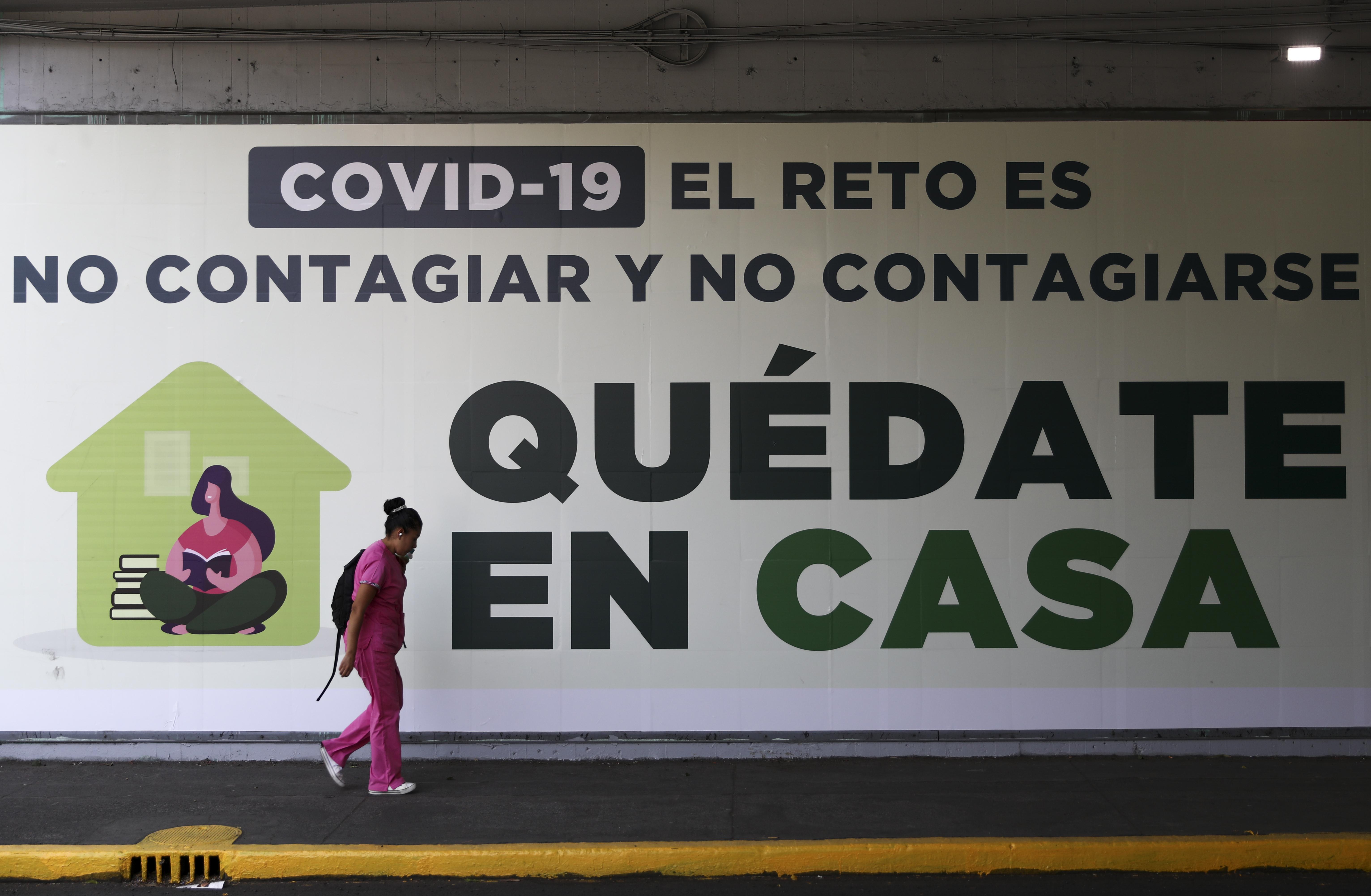 Una mujer pasa junto a un letrero que dice: