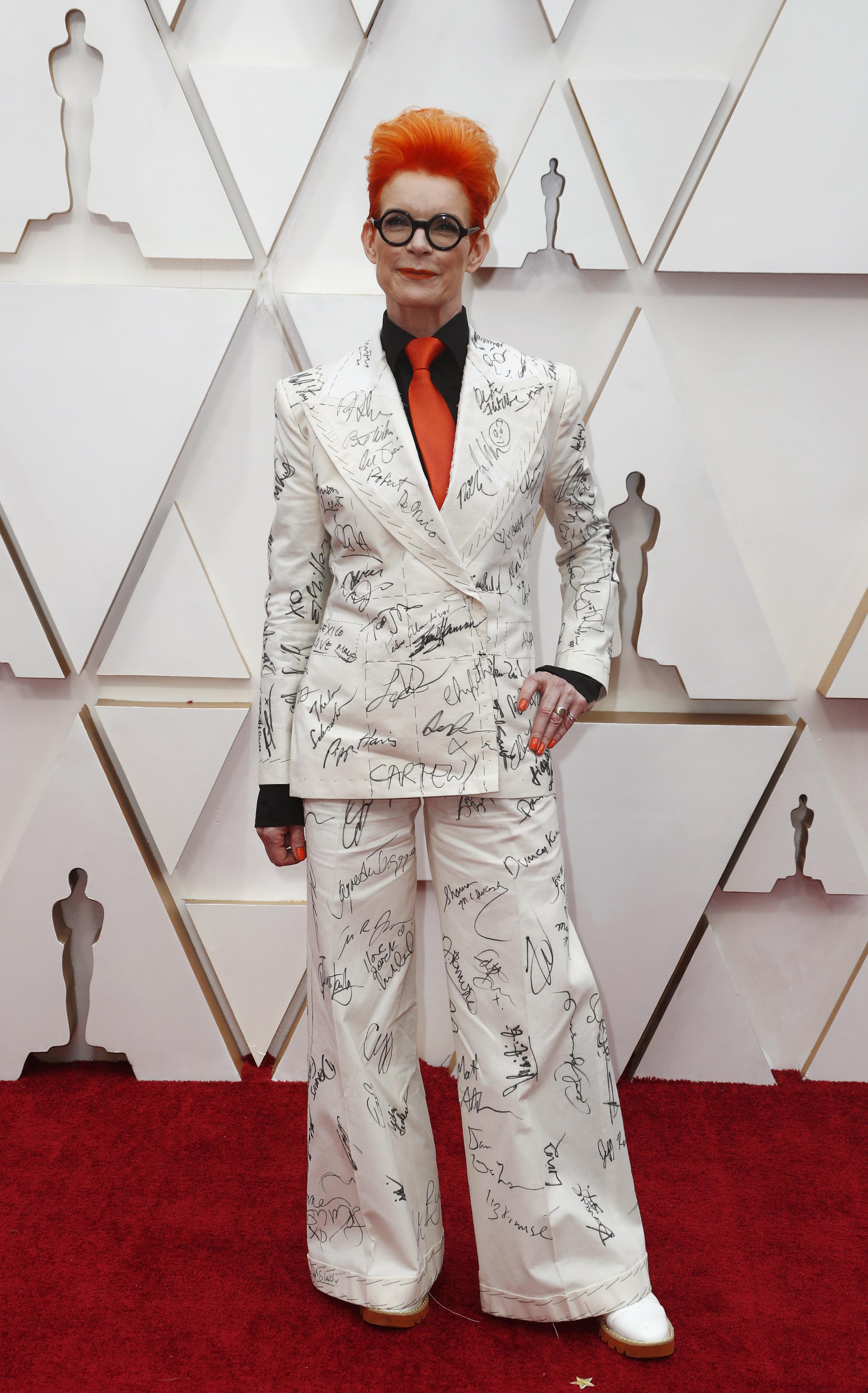 Sandy Powell fue uno de los looks más polémicos de la alfombra roja de los premios Oscar. Lució un traje estampado blanco con camisa negra y corbata naranja, haciendo juego con el color de su pelo