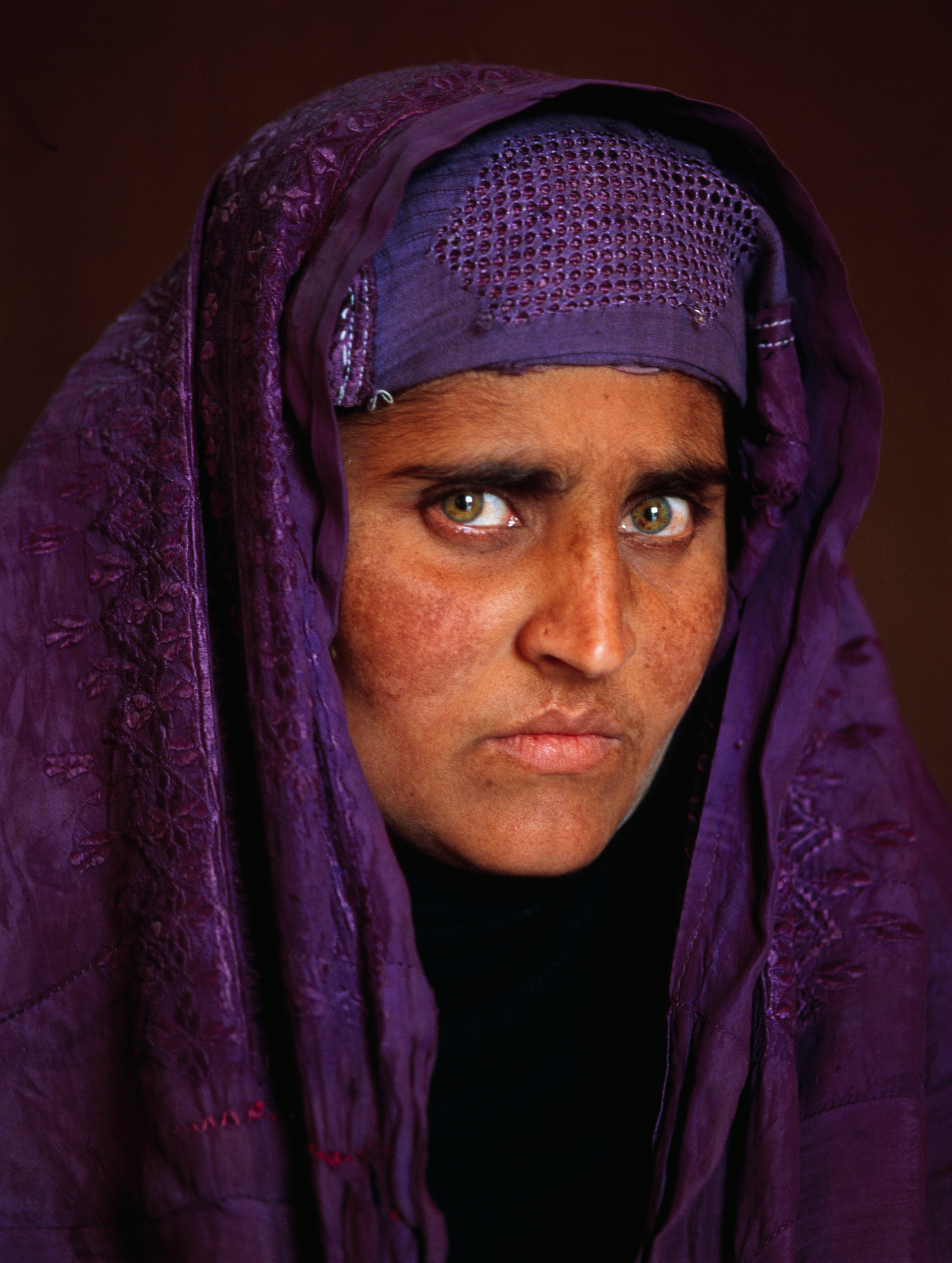 Dieciocho años después de su primera fotografía, Sharbat Gula, quien ahora vive en las montañas cercanas a Tora Bora, posa para la cámara otra vez. Steve McCurry, 2002