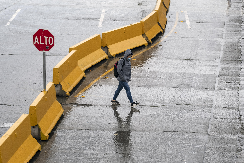 Una mujer usa una máscara facial mientras se dirige a los Estados Unidos en el puerto de entrada de San Ysidro en la frontera entre Estados Unidos y México en Tijuana, estado de Baja California, México, el 19 de marzo de 2020.
