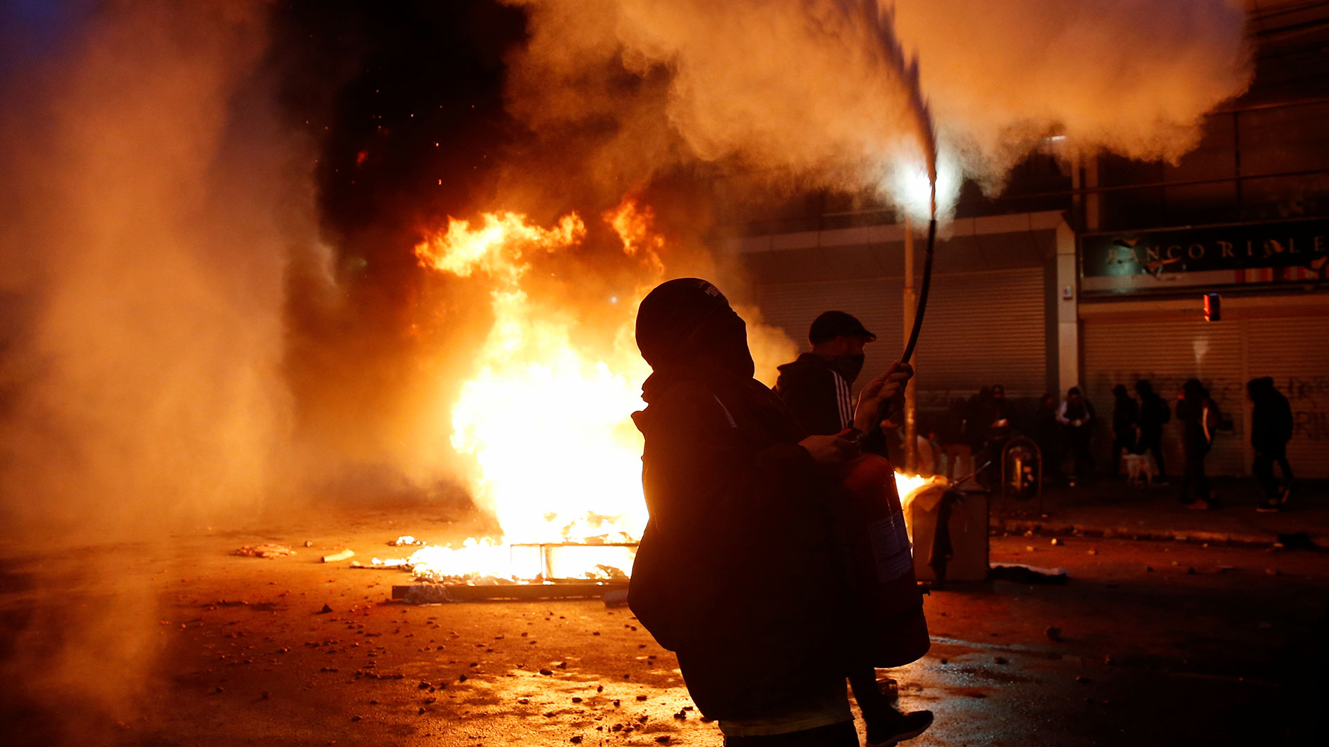 Manifestantes al rededor de una calle en llamas en Valparaíso.