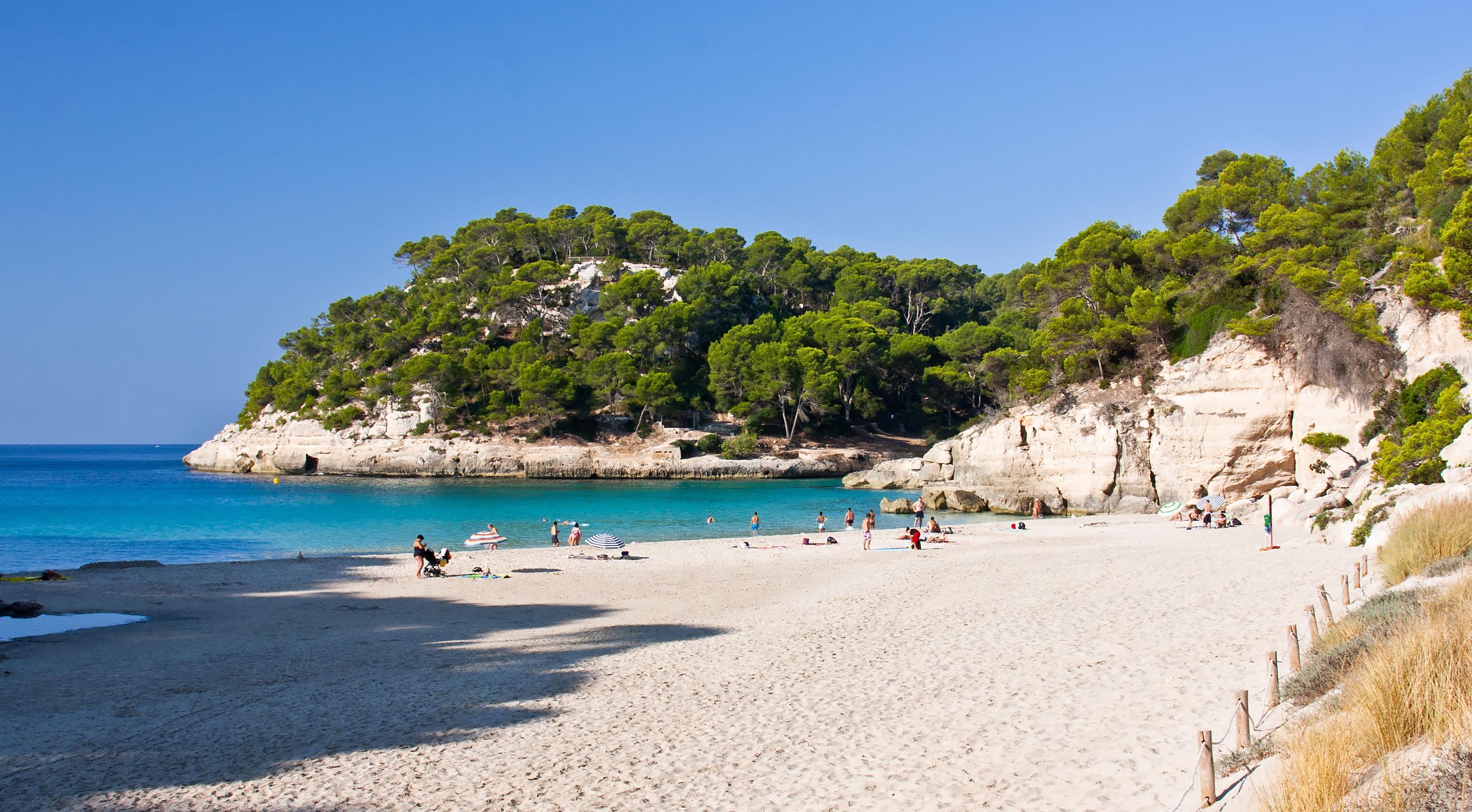 La gloriosa y vibrante playa de Cala Mitjana es la joya esmeralda de Menorca, España: el oasis español notable, anhelado y escondido que ofrece fantasías infinitas en un pequeño pedazo de paraíso. Los acantilados que se extienden por las costas son fáciles de escalar y poseen la altura ideal para sumergirse en las maravillosas aguas debajo