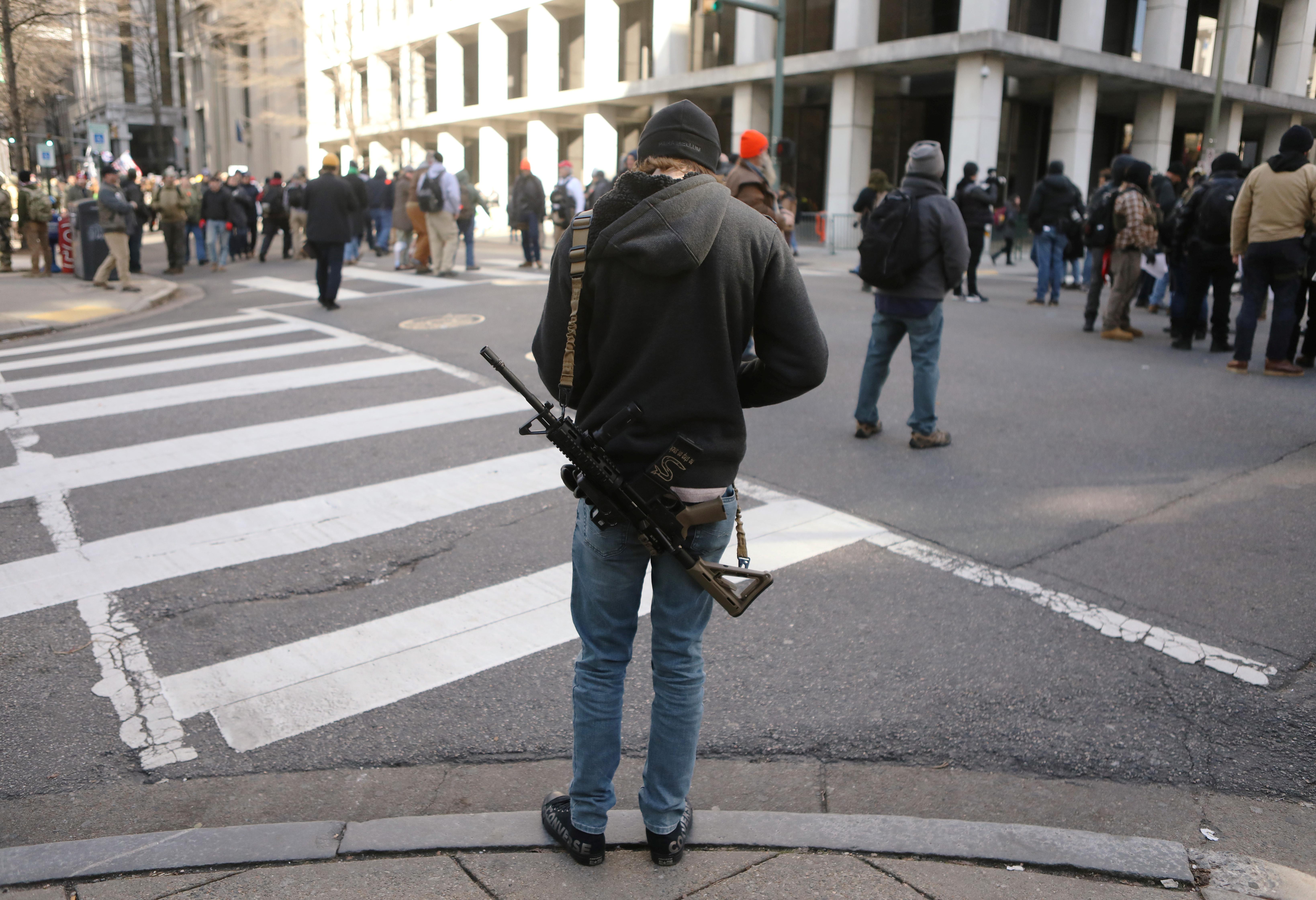 Otro fusil de la familia del AR-15, uno de los más populares en Estados Unidos, cuelga del hombro de un asistente (REUTERS/Jim Urquhart)