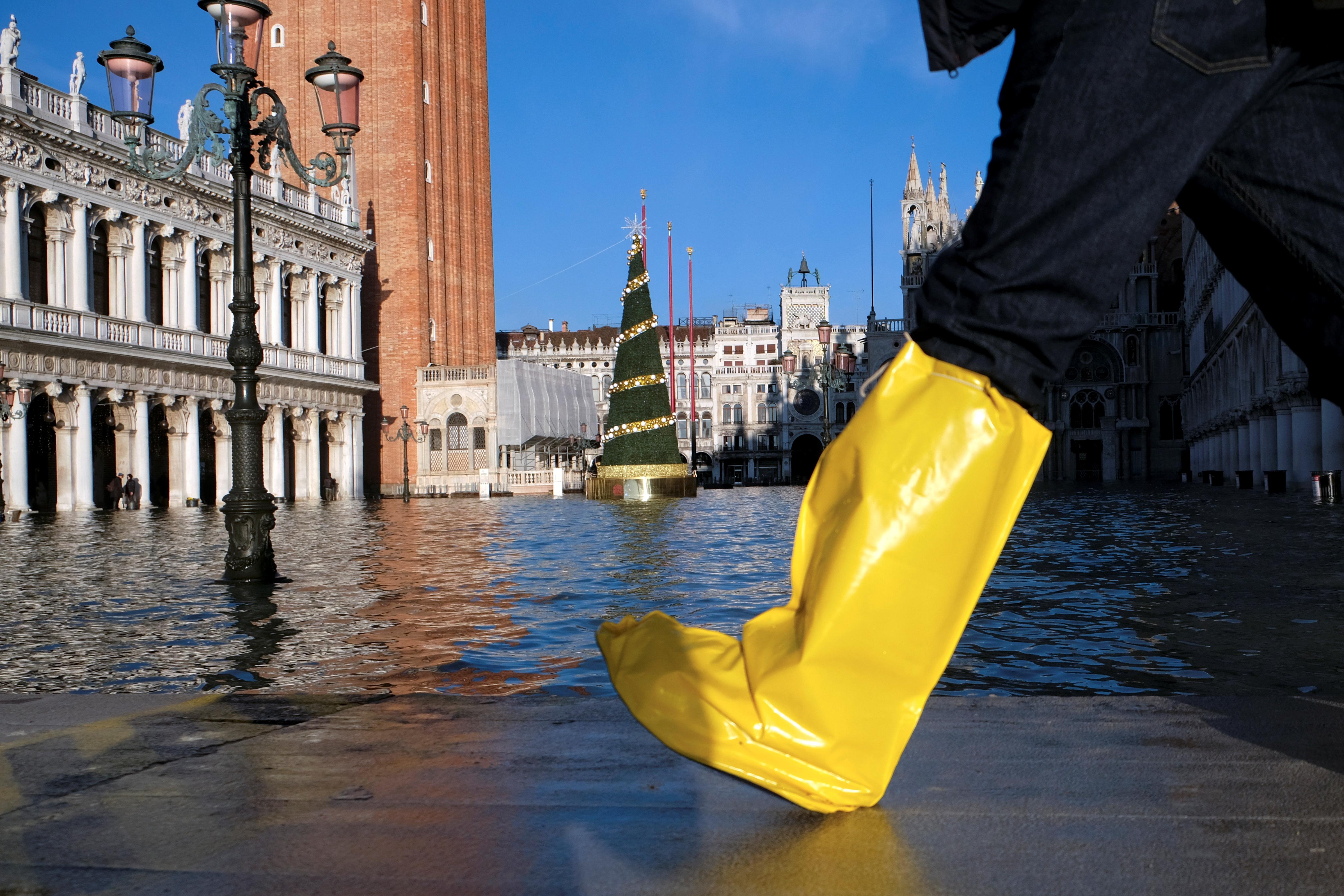 Una persona camina en la Plaza de San Marcos durante la marea alta en Venecia, Italia, el 24 de diciembre de 2019 (REUTERS/Manuel Silvestri)