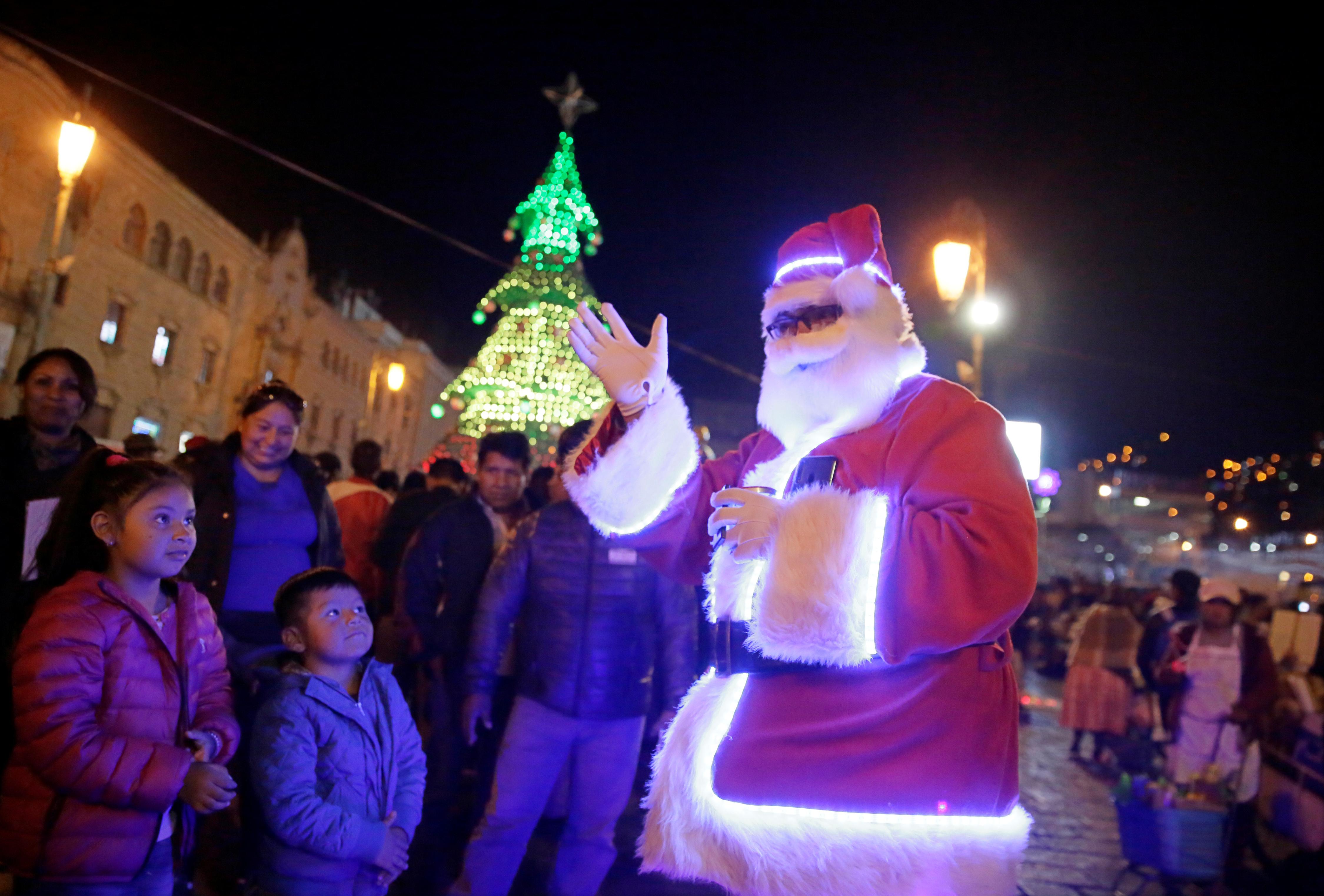 Un hombre vestido como Santa Claus saluda en la plaza San Francisco durante la temporada navideña en La Paz, Bolivia, el 22 de diciembre de 2019 (Reuters/ David Mercado)