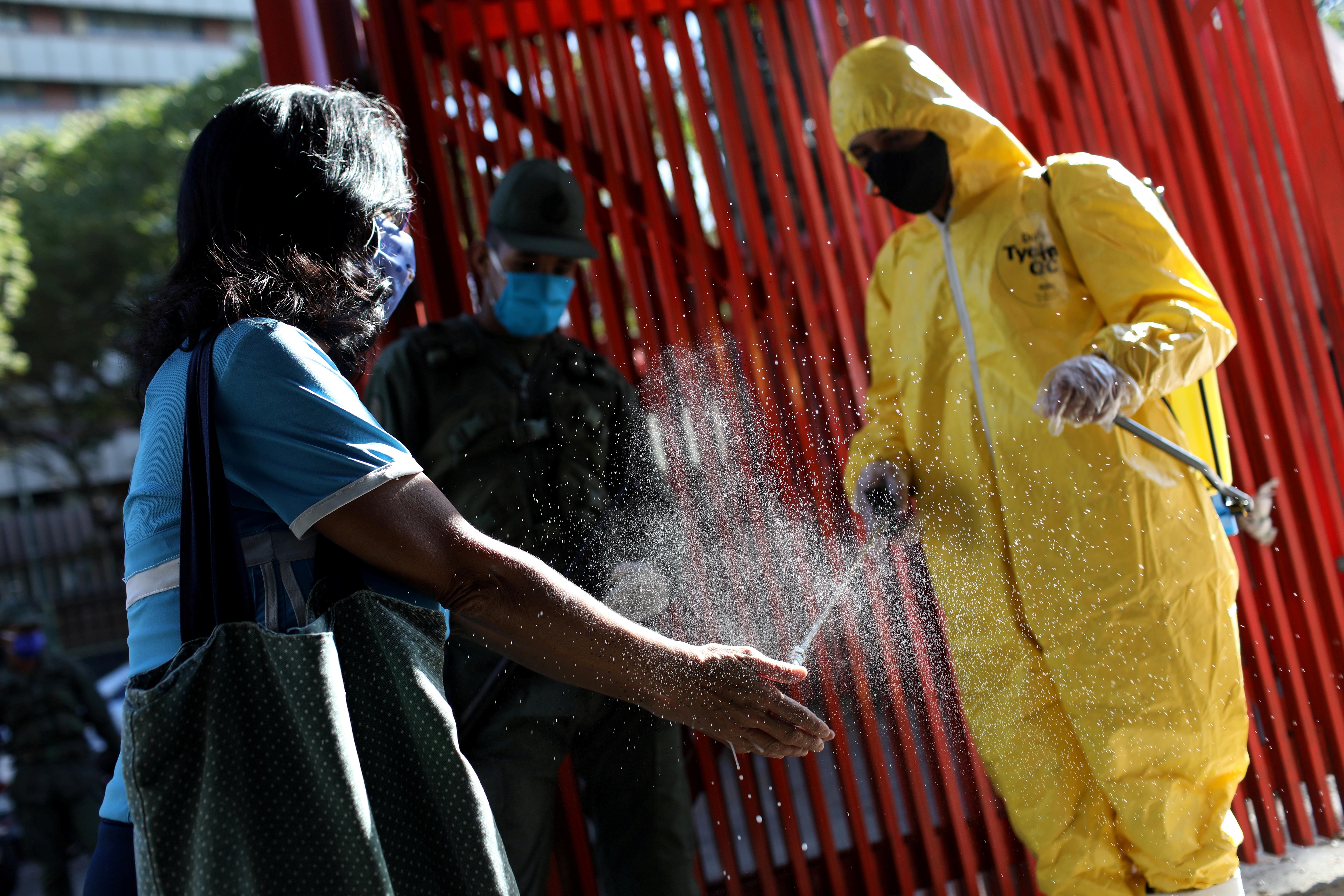 Un trabajador limpia las manos de una venezolana en Caracas (REUTERS/Manaure Quintero)