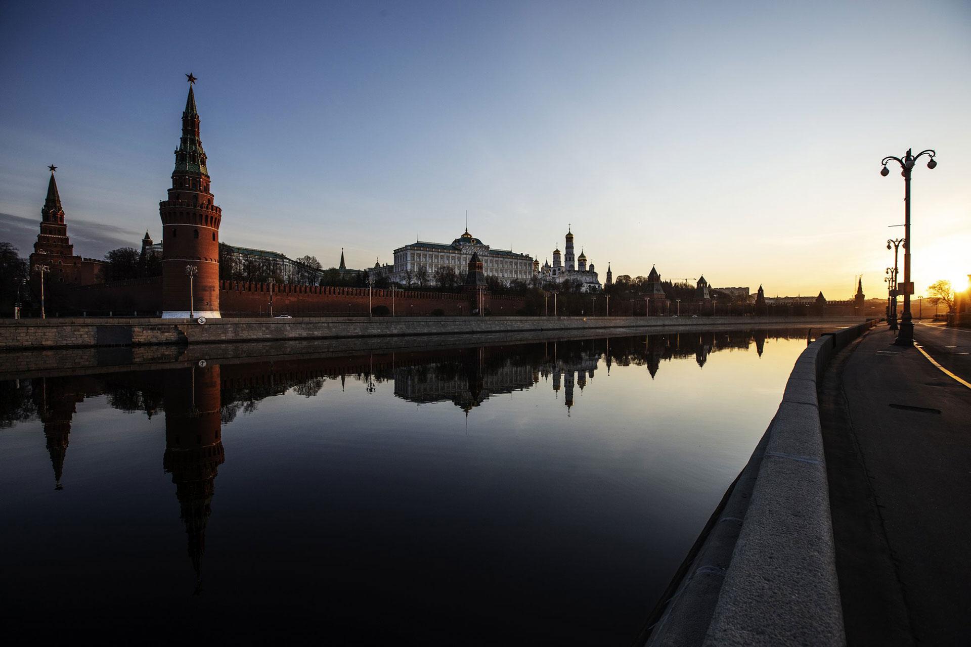 El Kremlin y sus torres se reflejan en el río Moscú a lo largo de un terraplén desierto cuando sale el sol sobre la capital de Rusia, el lunes 27 de abril de 2020. (Foto AP / Alexander Zemlianichenko)