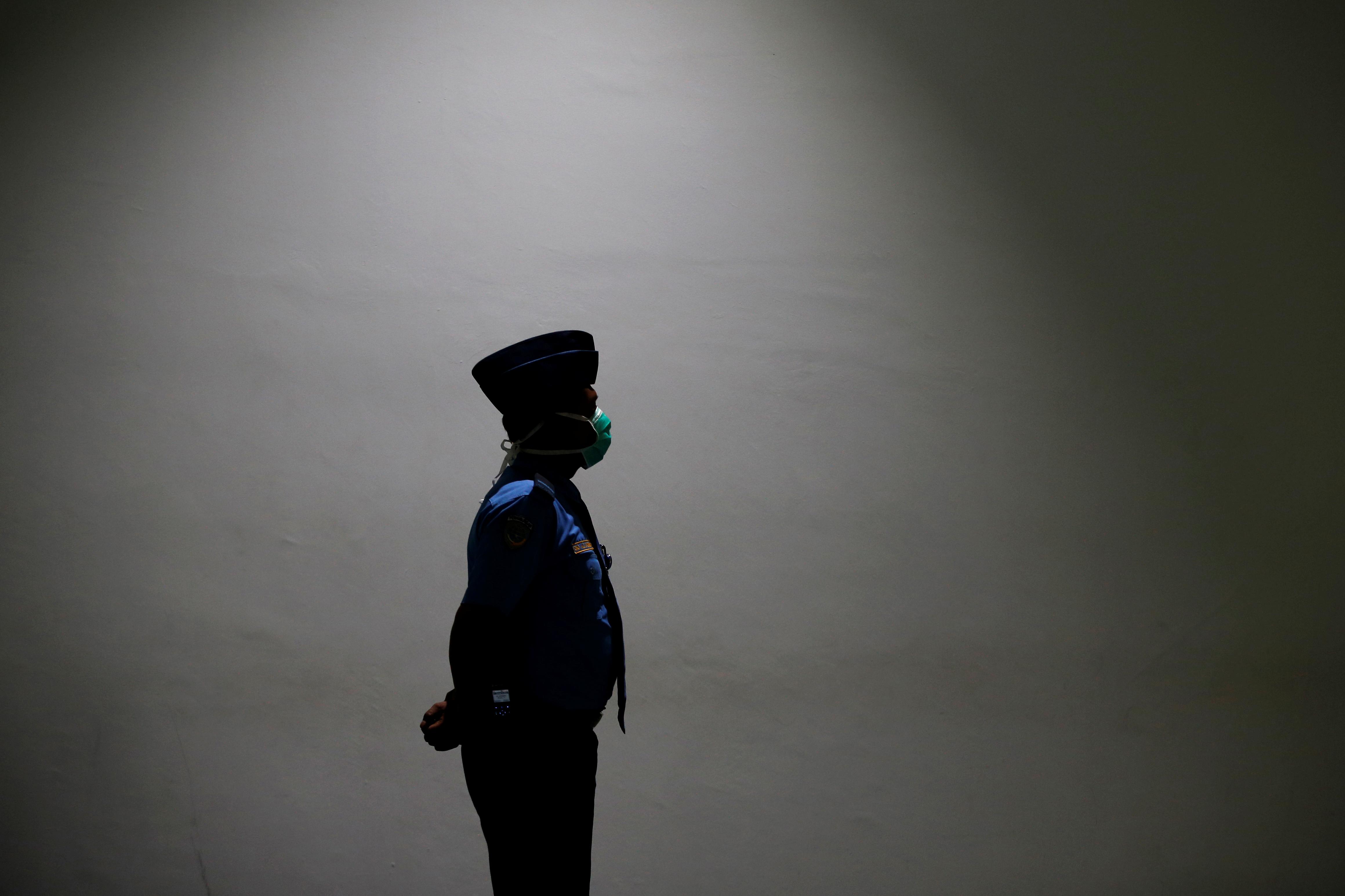 Un oficial de seguridad de aviación con máscara médica está de pie mientras protege en la terminal de llegadas internacionales del aeropuerto Soekarno Hatta cerca de Yakarta, Indonesia, el 21 de enero de 2020. REUTERS / Willy Kurniawan