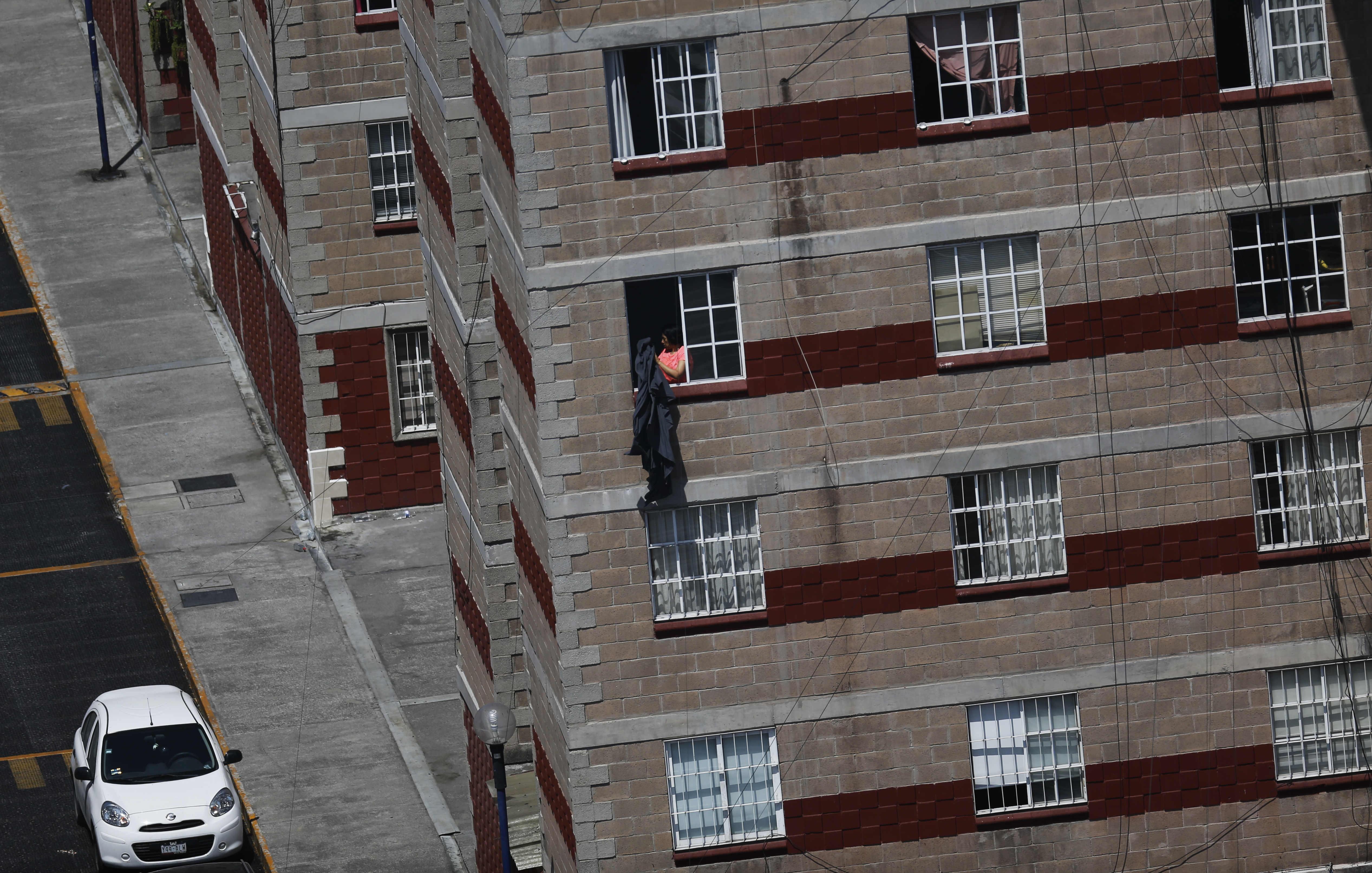 Una persona sacude una manta desde la ventana de su departamento en la Ciudad de México, el martes 31 de marzo de 2020.