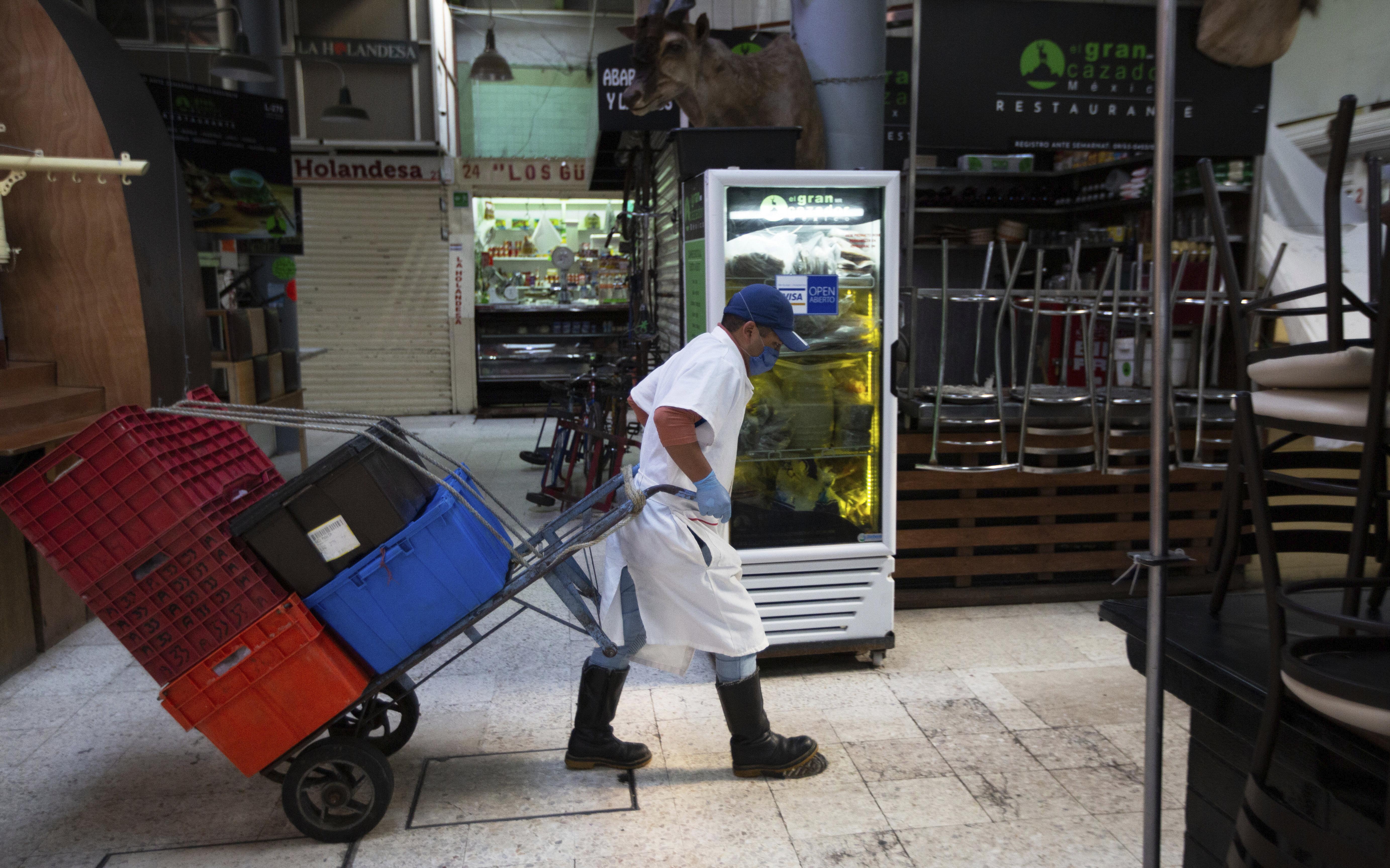 Un empleado que usa una mascarilla protectora y guantes desechables, transporta cajas con la ayuda de un carrito a través del popular y normalmente concurrido mercado de alimentos de San Juan, en la Ciudad de México, el miércoles 25 de marzo de 2020.