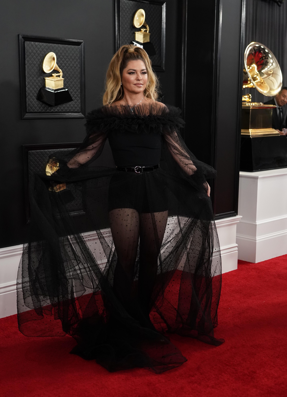 Shania Twain - Lució un vestido de plumeti negro, escote of shoulders, con cinturón