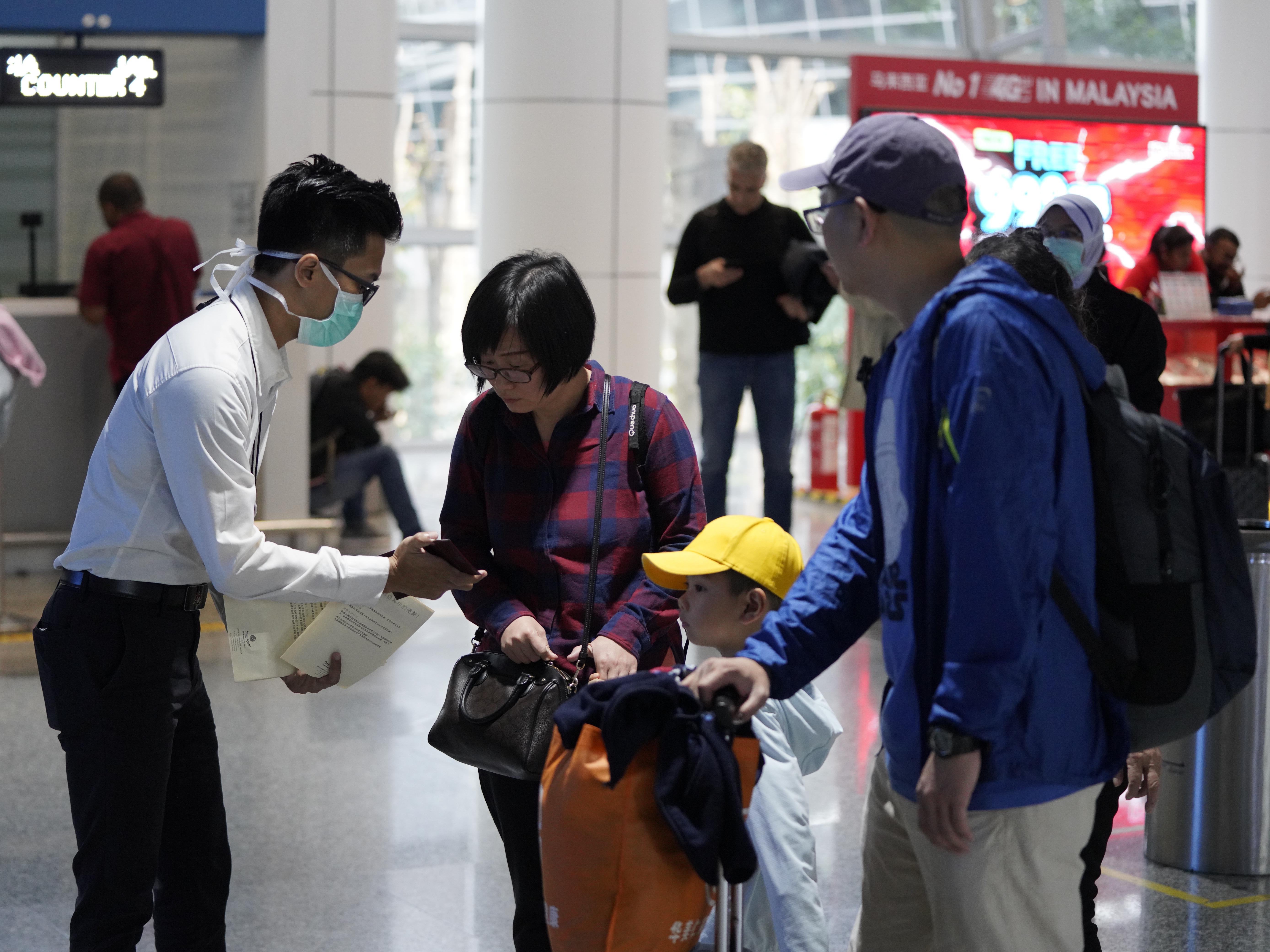 Los funcionarios de salud revisan a los pasajeros en el aeropuerto internacional de Kuala Lumpur en Sepang, Malasia, el martes 21 de enero de 2020. Países tanto en Asia-Pacífico como en otros lugares han iniciado controles de temperatura corporal en aeropuertos, estaciones de ferrocarril y autopistas con la esperanza de atraparlos. en riesgo de portar un nuevo coronavirus que ha enfermado a más de 200 personas en China. (Foto AP / Vincent Thian)