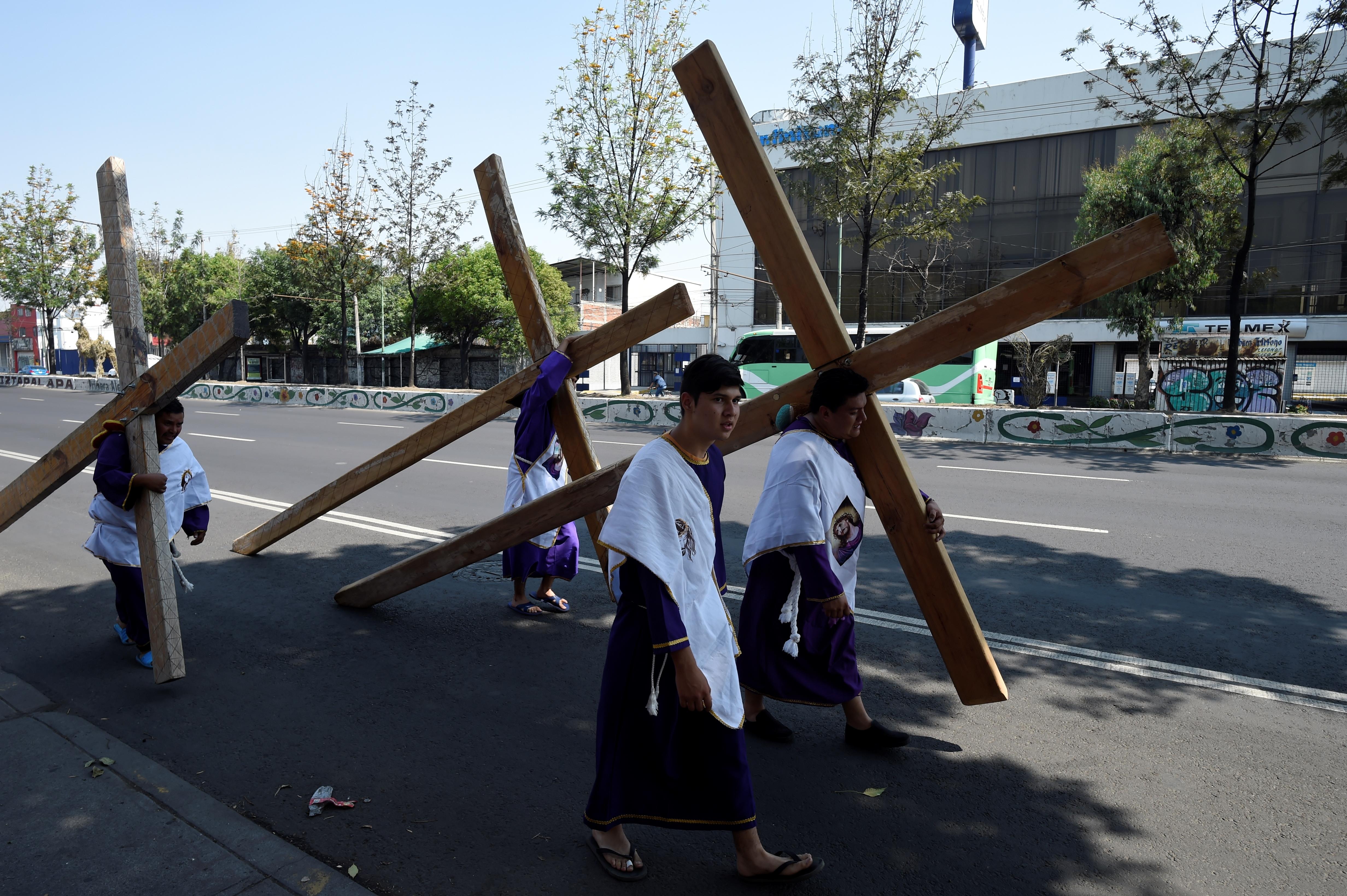 Nazarenos cargando sus cruces en las calles vacías de la alcaldía de Iztapalapa durante las celebraciones de Semana Santa (Foto: Alfredo Estrella/AFP)
