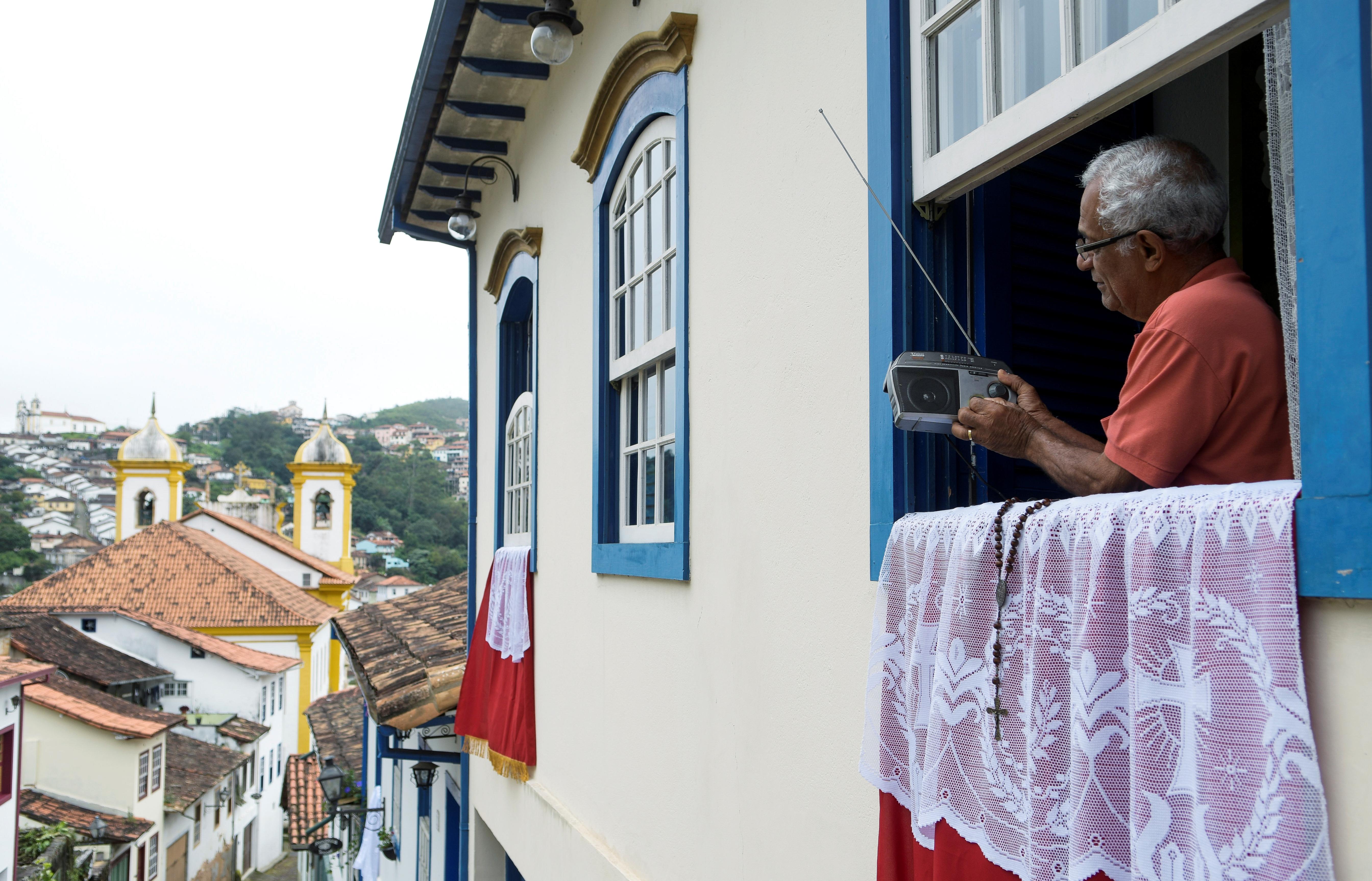 Un residente de Ouro Preto sigue la misa local por radio, en el medio de la pandemia por COVID-19