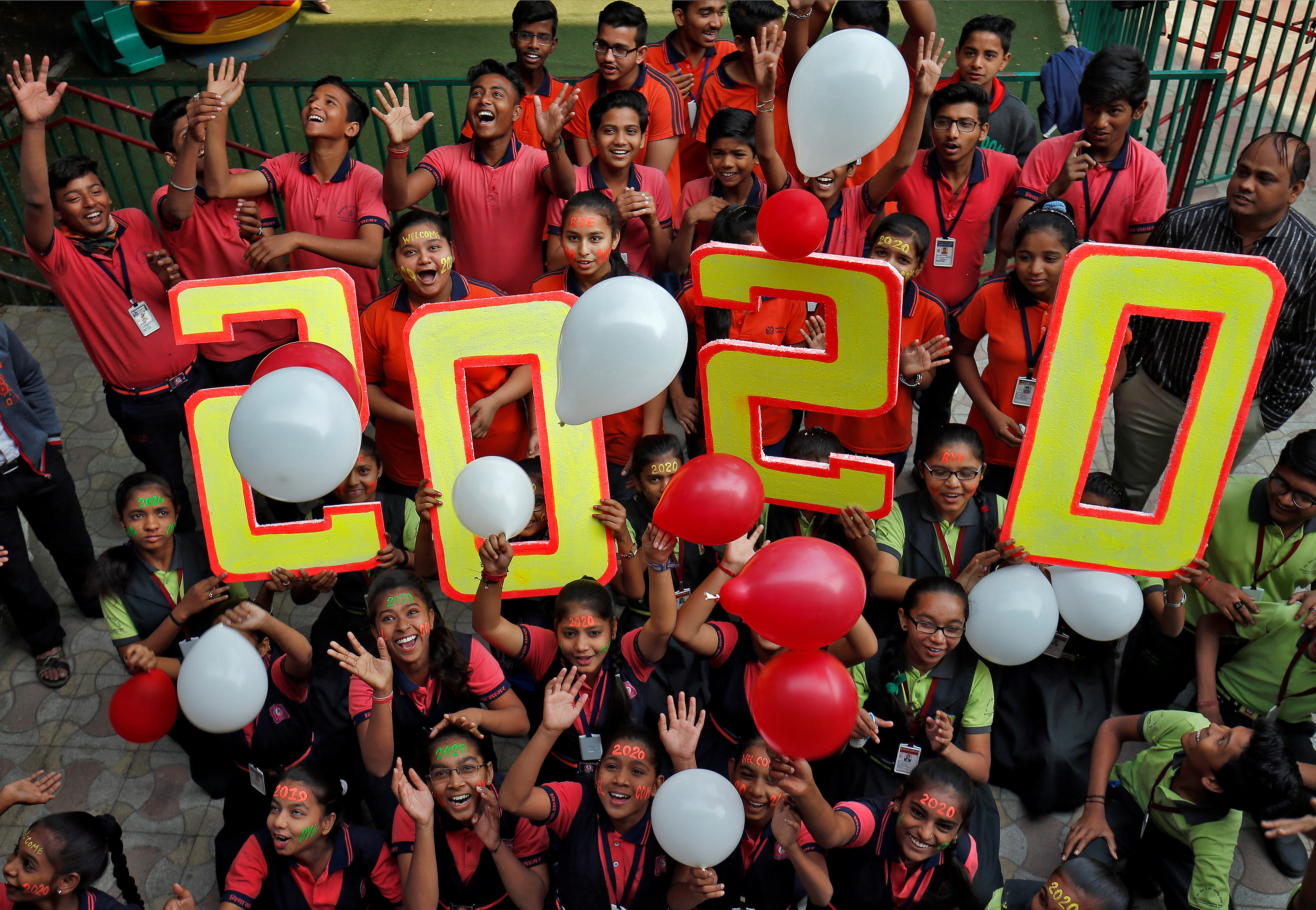 Alumnos de una escuela de Ahmedabad, India, celebran la llegad adel 2020.