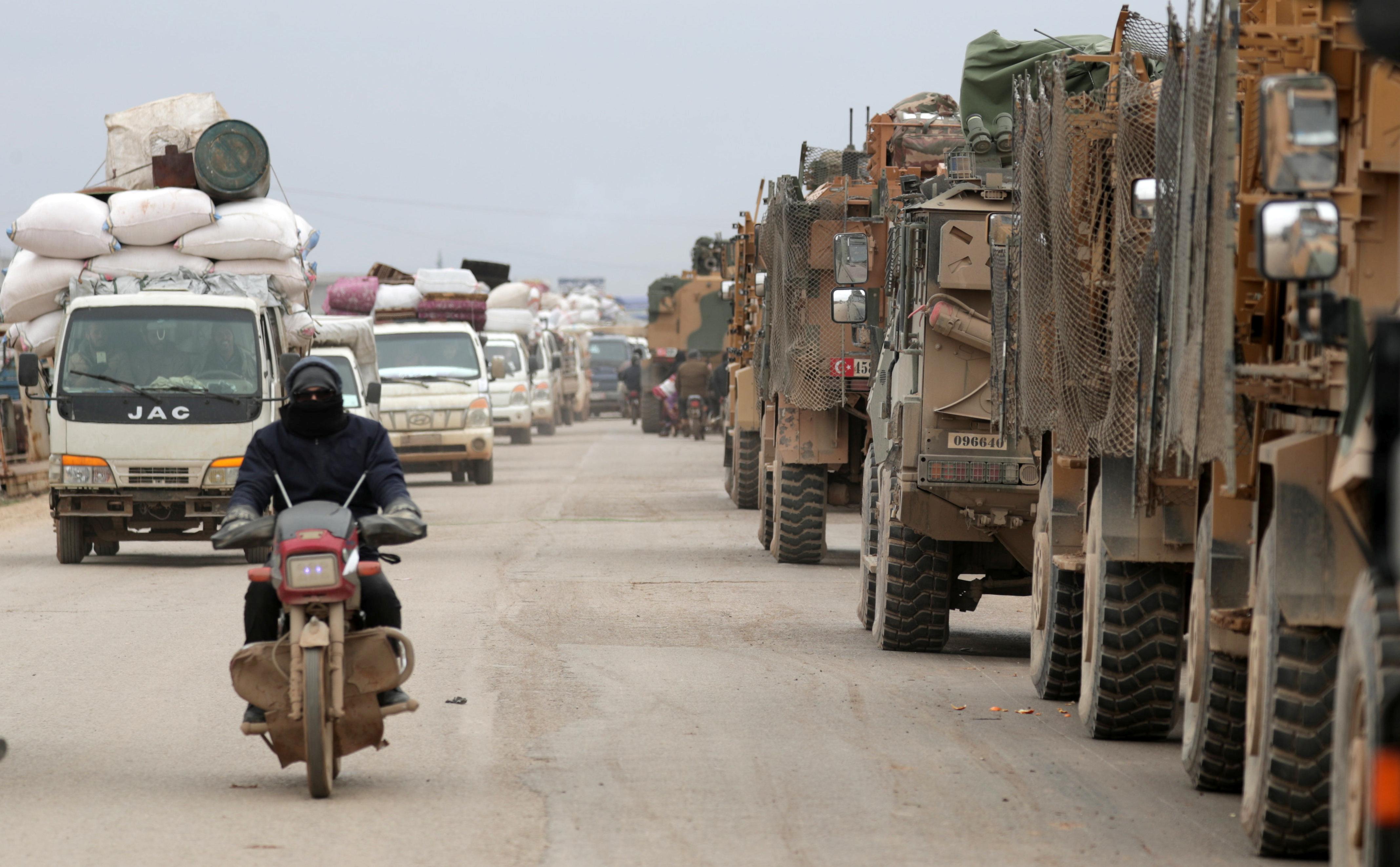 Una columna de civiles avanza en dirección contrario a los camiones y blindados turcos que se dirigen al encuentro con el régimen sirio