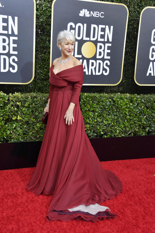 Helen Mirren impactó con su vestido color borravino de cuello bote y cruzado con cola. Completó su look con clutch rígido a tono, una gargantilla en punta y un brazalete de brillantes