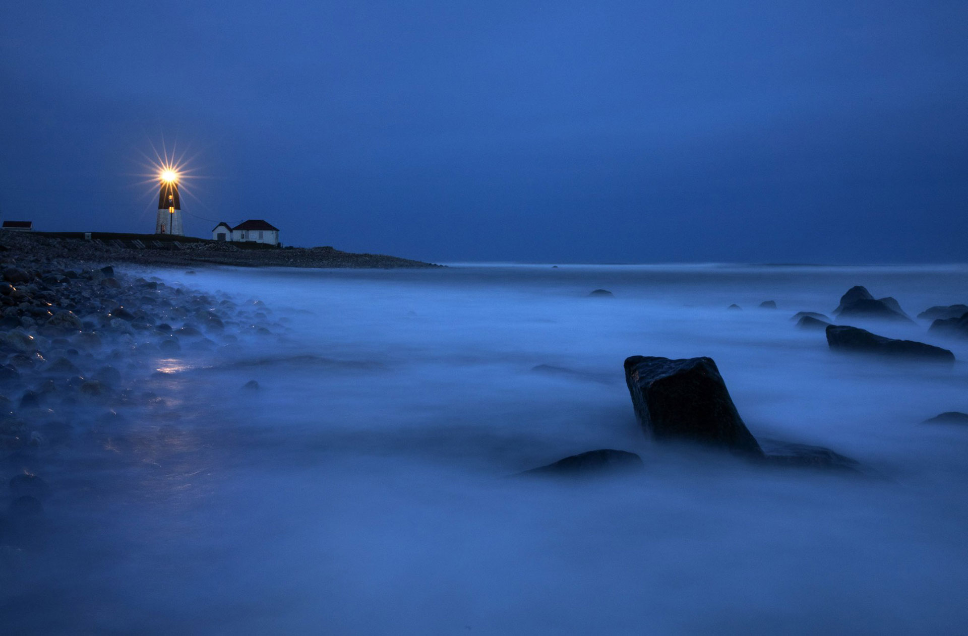 Las olas bañan las rocas cuando un faro de luz brilla a través de la costa rocosa desde el faro de Point Judith en Narragansett, Rhode Island, EEUU, el sábado 25 de abril de 2020. (Foto AP / David Goldman)