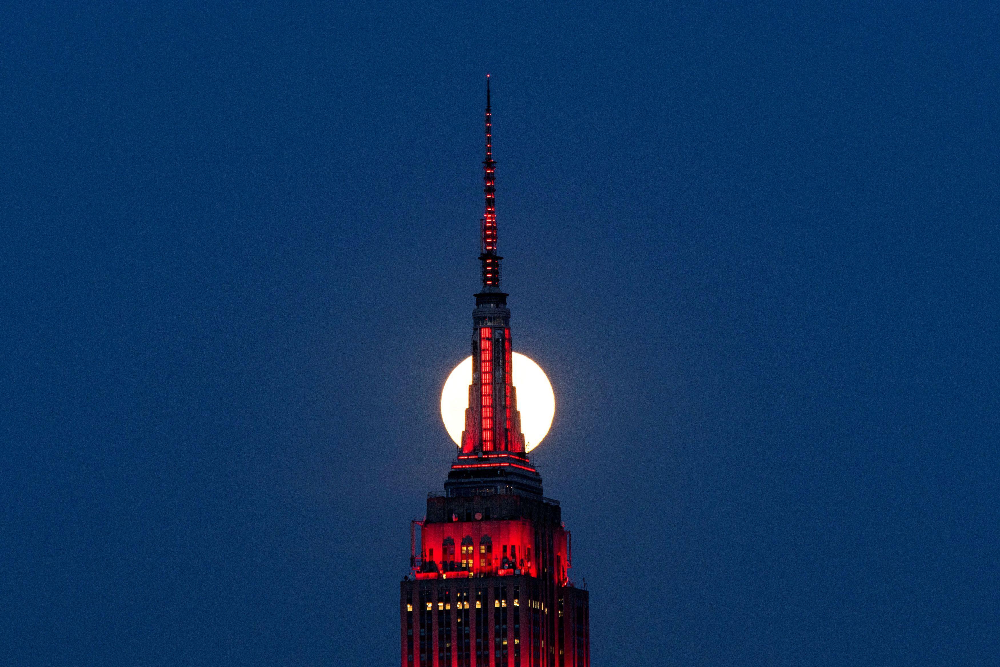 La Superluna se eleva detrás del Empire State Building mientras se ilumina en rojo en solidaridad con las personas infectadas con el coronavirus vista desde Hoboken, Nueva Jersey (REUTERS / Eduardo Munoz)