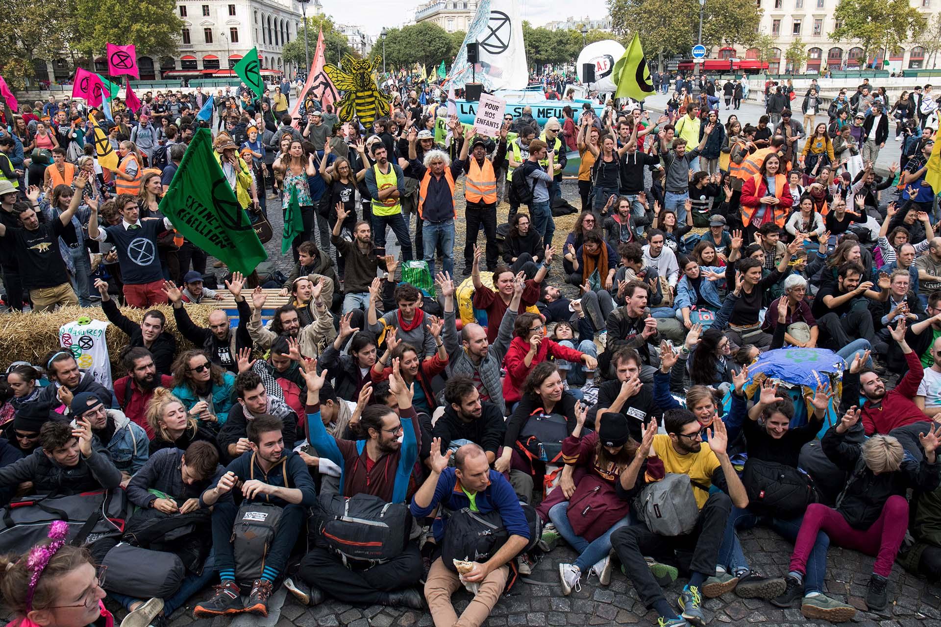 Los manifestantes se sientan en el suelo para bloquear el puente Pont au Change durante una manifestación convocada por el grupo activista del cambio climático Extinction Rebellion, el 7 de octubre de 2019 frente a la Conciergerie en París. (AFP)