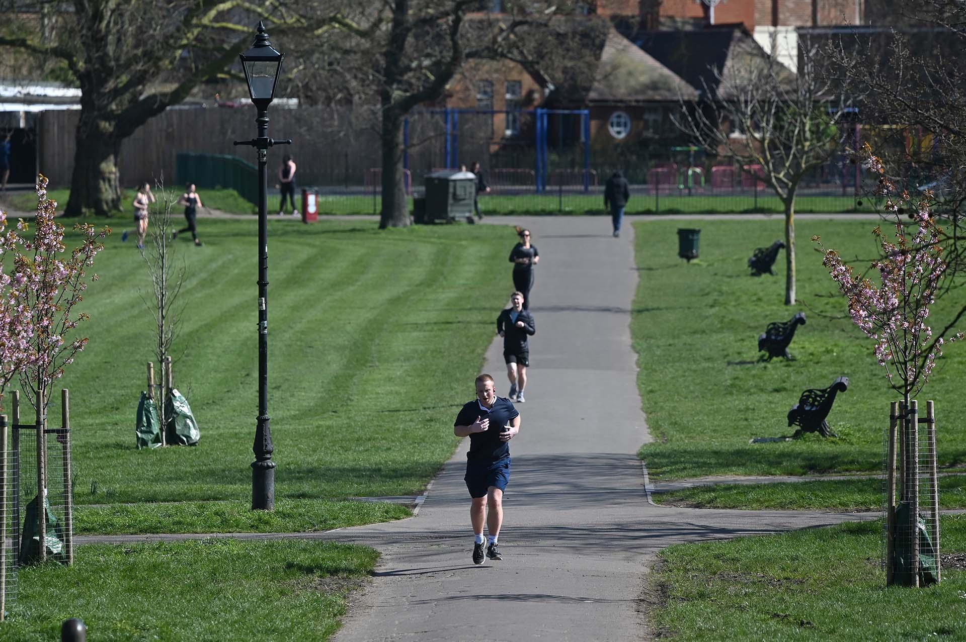 Corredores se ejercitan a distancia en el parque de Clapham Common en el sur de Londres. (AFP)