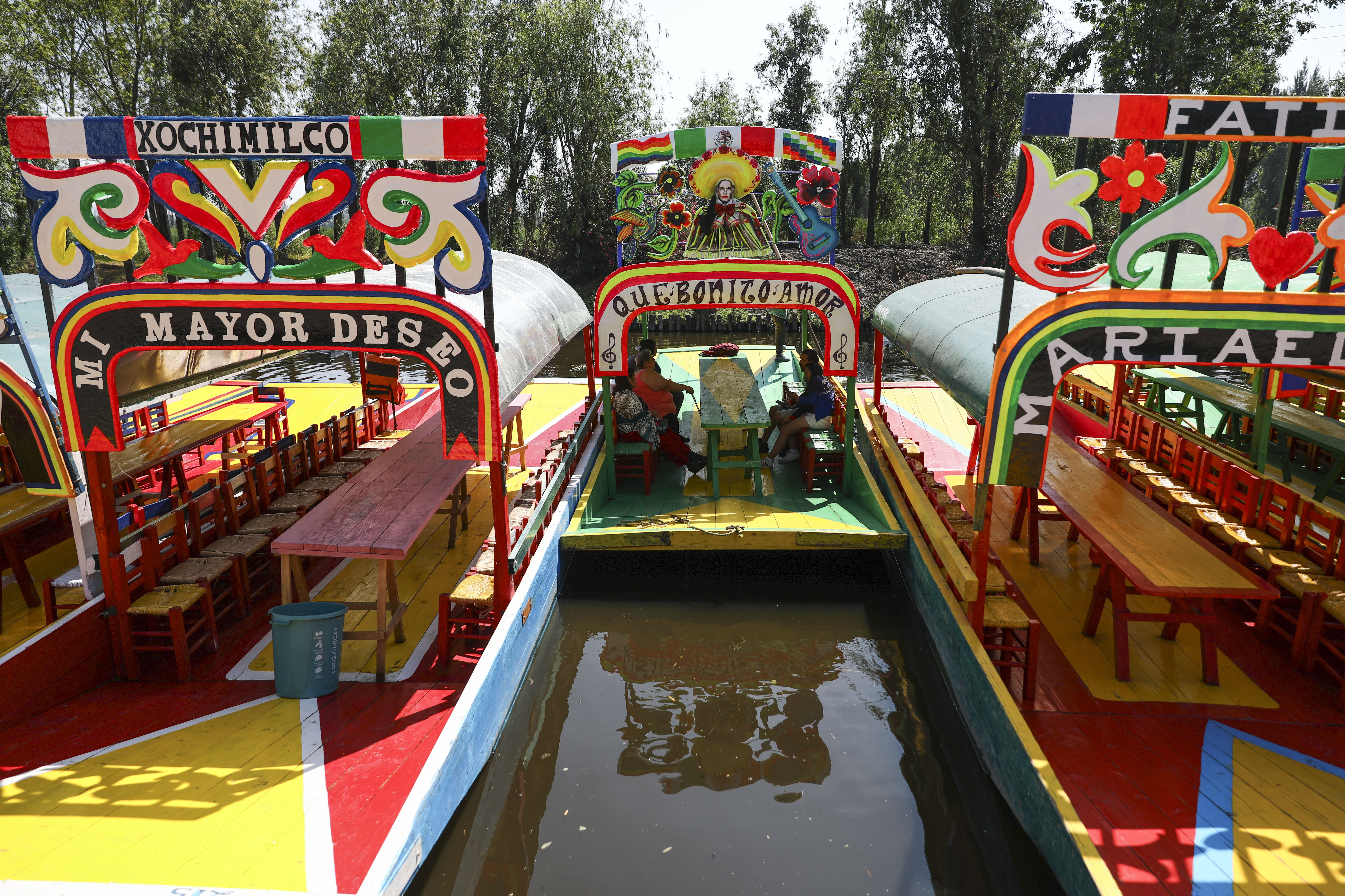 Los visitantes viajan en una trajinera, uno de los botes de madera pintados populares entre los turistas que recorren los canales en el distrito de Xochimilco de la Ciudad de México, el domingo 22 de marzo de 2020.