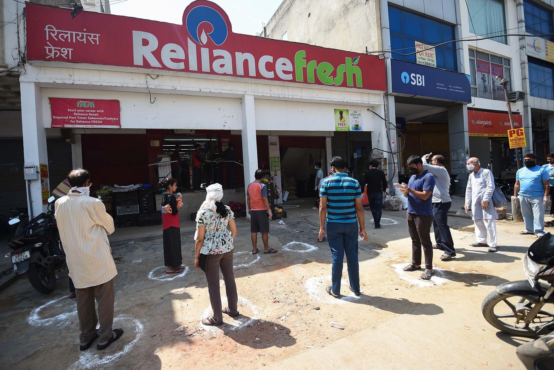 Personas hacen fila frente a un mercadillo en Faridabad, India.