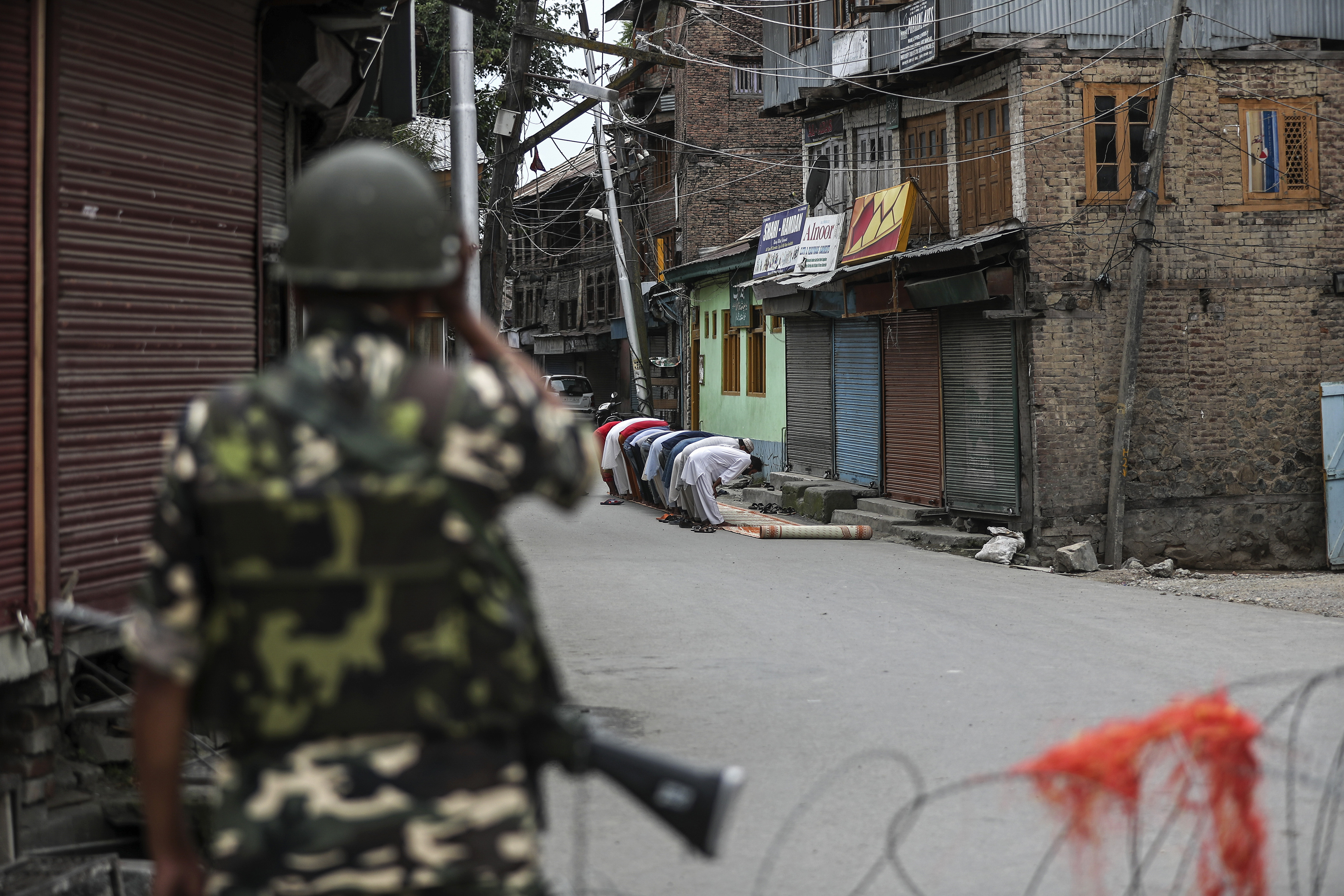 Un soldado paramilitar indio está de guardia mientras los musulmanes de Cachemira ofrecen oraciones los viernes en una calle frente a una mezquita local durante el toque de queda como restricciones en Srinagar, India, el 16 de agosto de 2019. (Foto AP / Mukhtar Khan)