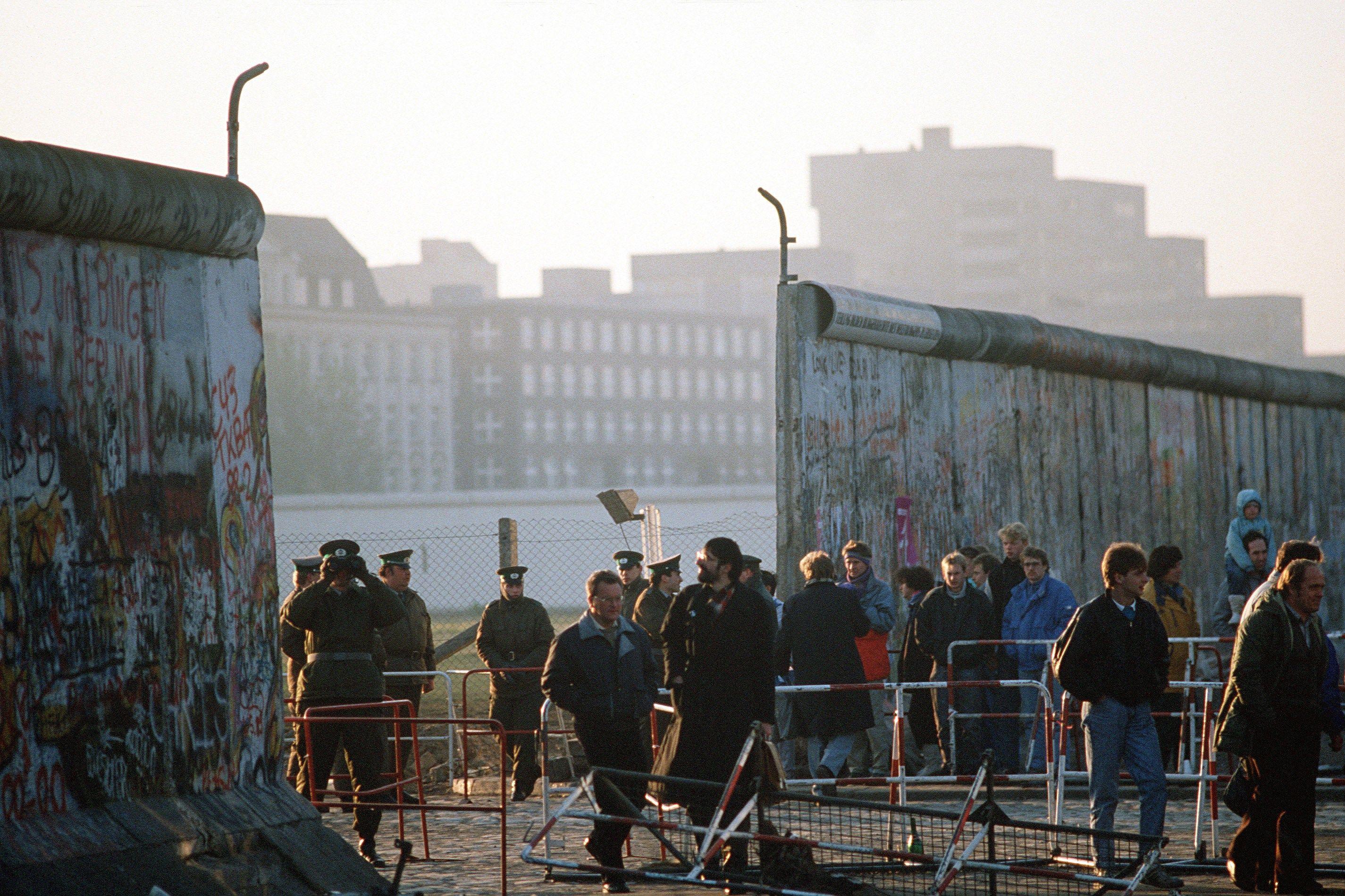 Policías de Alemania Oriental observan el paso de personas en una de las aperturas de libre tránsito abiertas en el muro. 14 de noviembre de 1989 a la altura de Potsdamer Platz