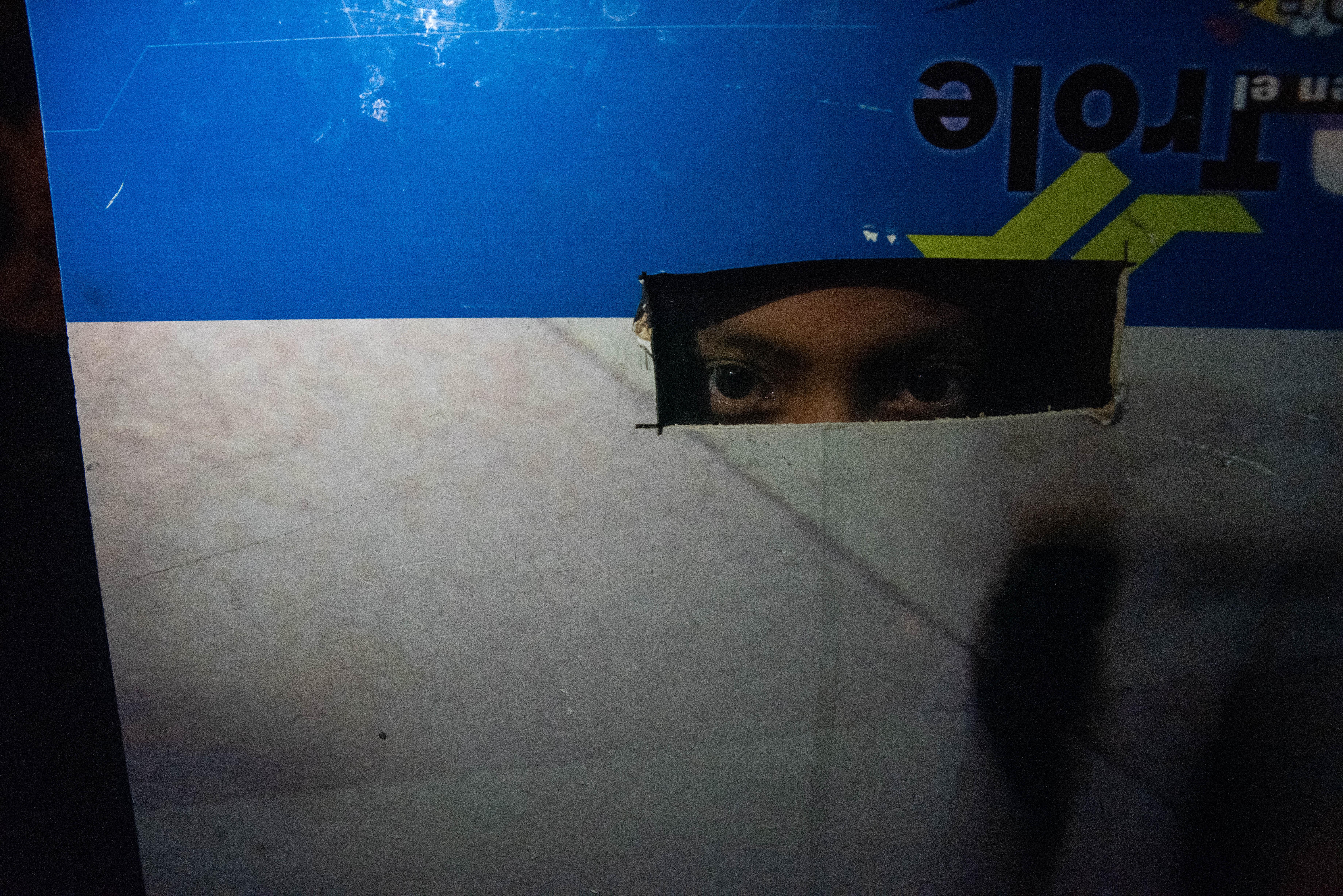 Un niño mira a través de un agujero de un pedazo de cartón que había utilizado para protegerse de la policía durante las manifestaciones que duraron doce días en Quito, Ecuador.