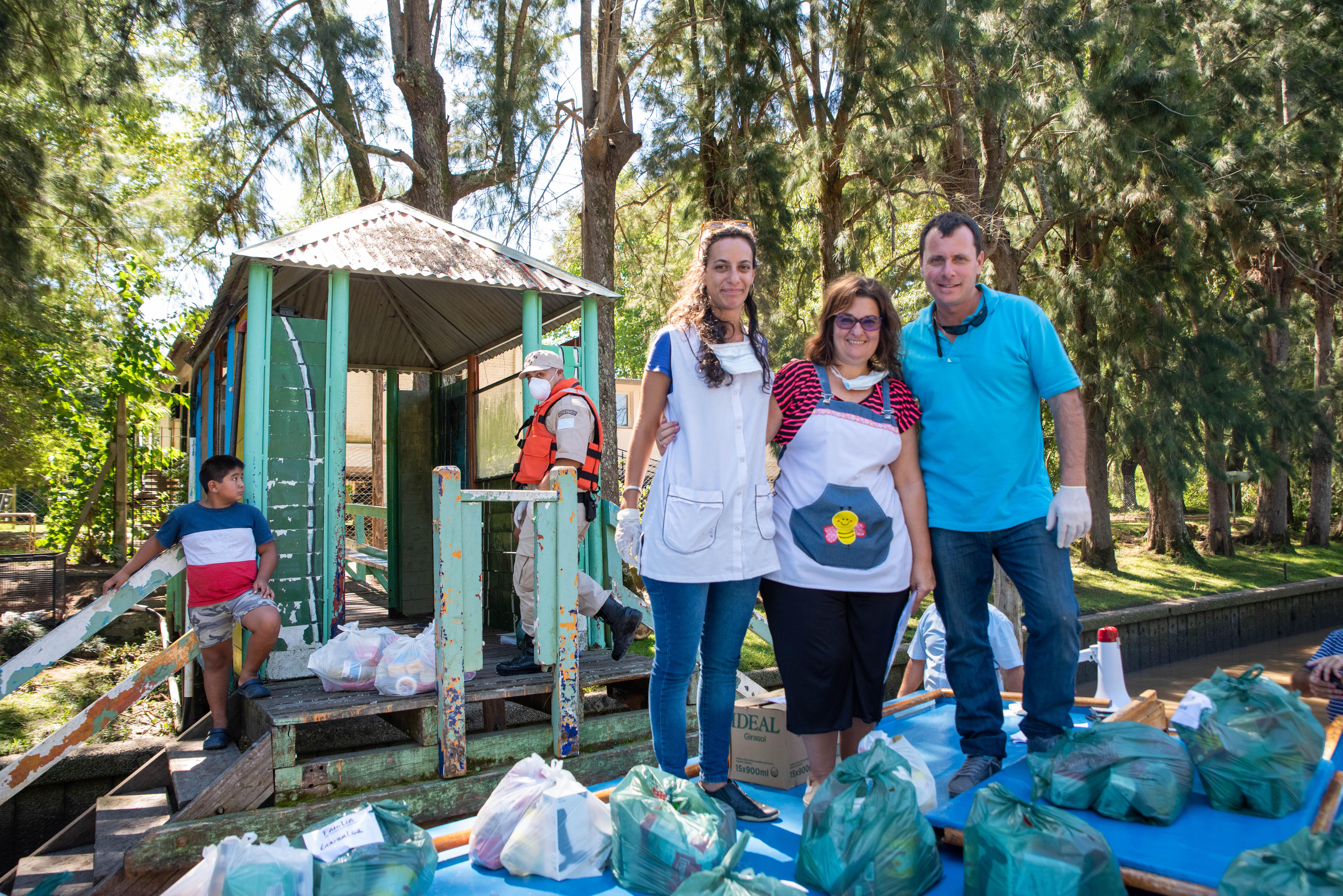 Paula, Graciela y Diego frente a la escuela donde imparten sus clases repartiendo las bolsas de alimentos. (Foto: Franco Fafasuli)