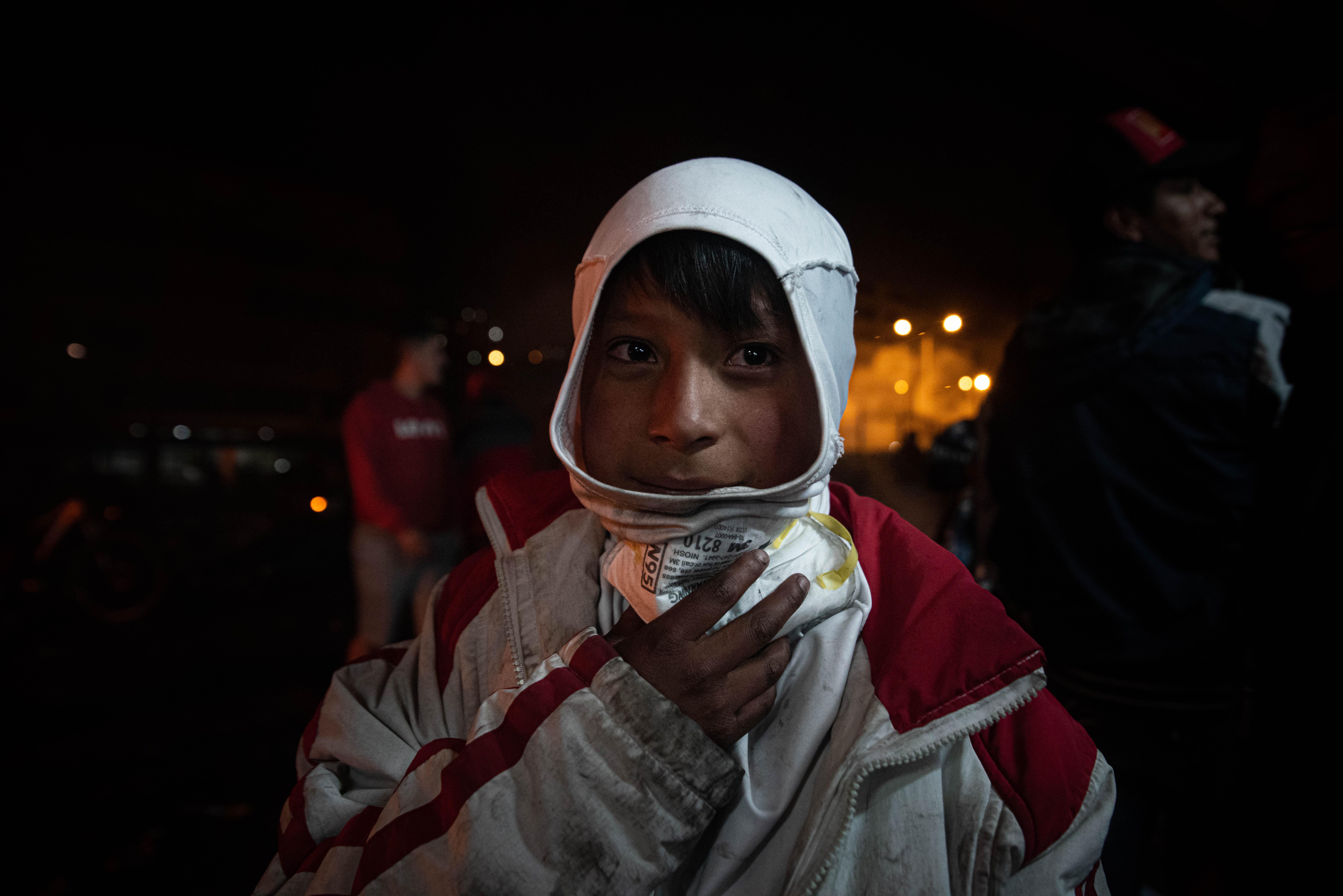 Un niño con una mascara respiratoria celebra en las calles de Quito