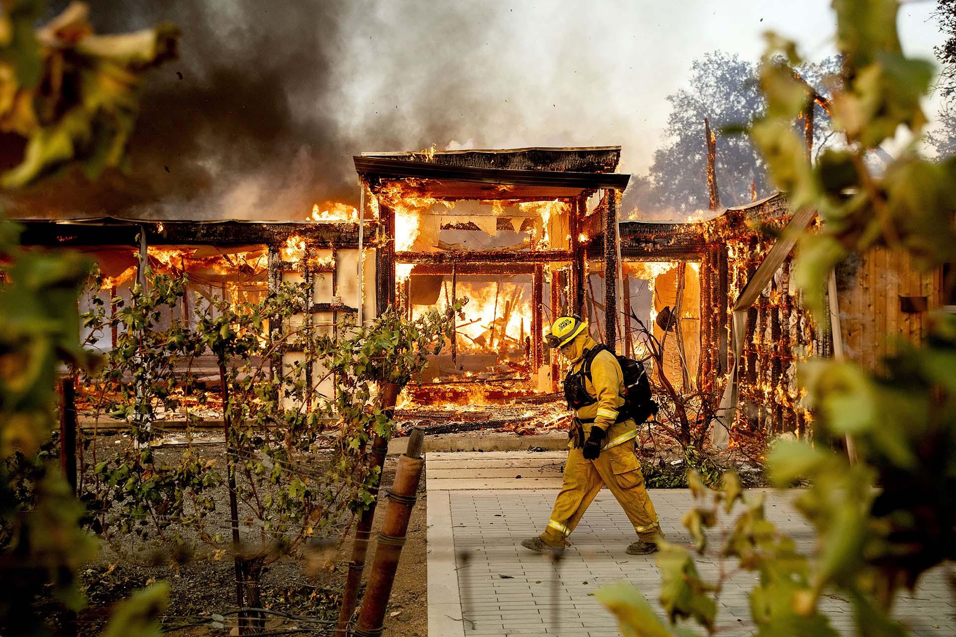 El bombero de Woodbridge Joe Zurilgen pasa por una casa en llamas mientras el incendio de Kincade se desata en Healdsburg, California