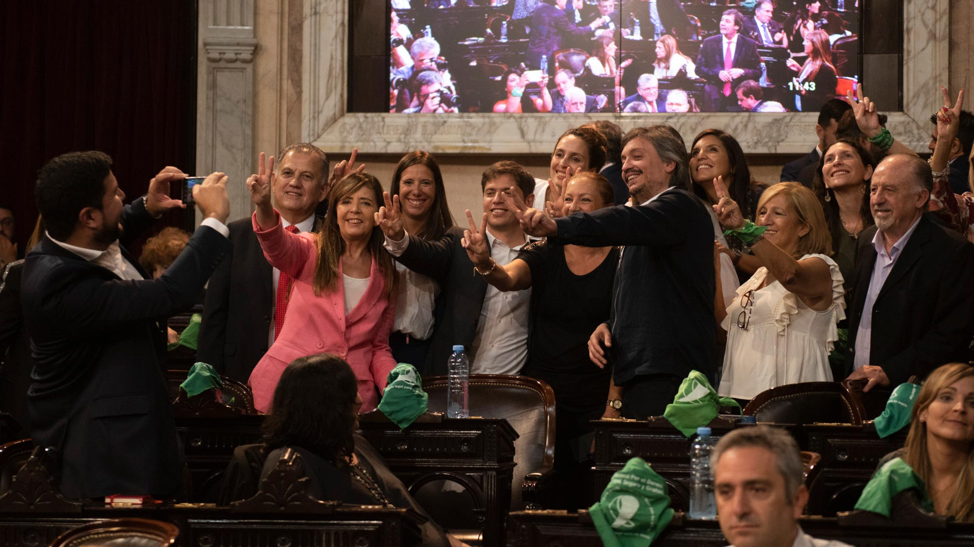 Axel Kicillof, el gobernador de la provincia de Buenos Aires, en medio de otros funcionarios oficialistas haciendo la señal peronista y acompañado también por otros símbolos relativos a la causa por la legalización del aborto