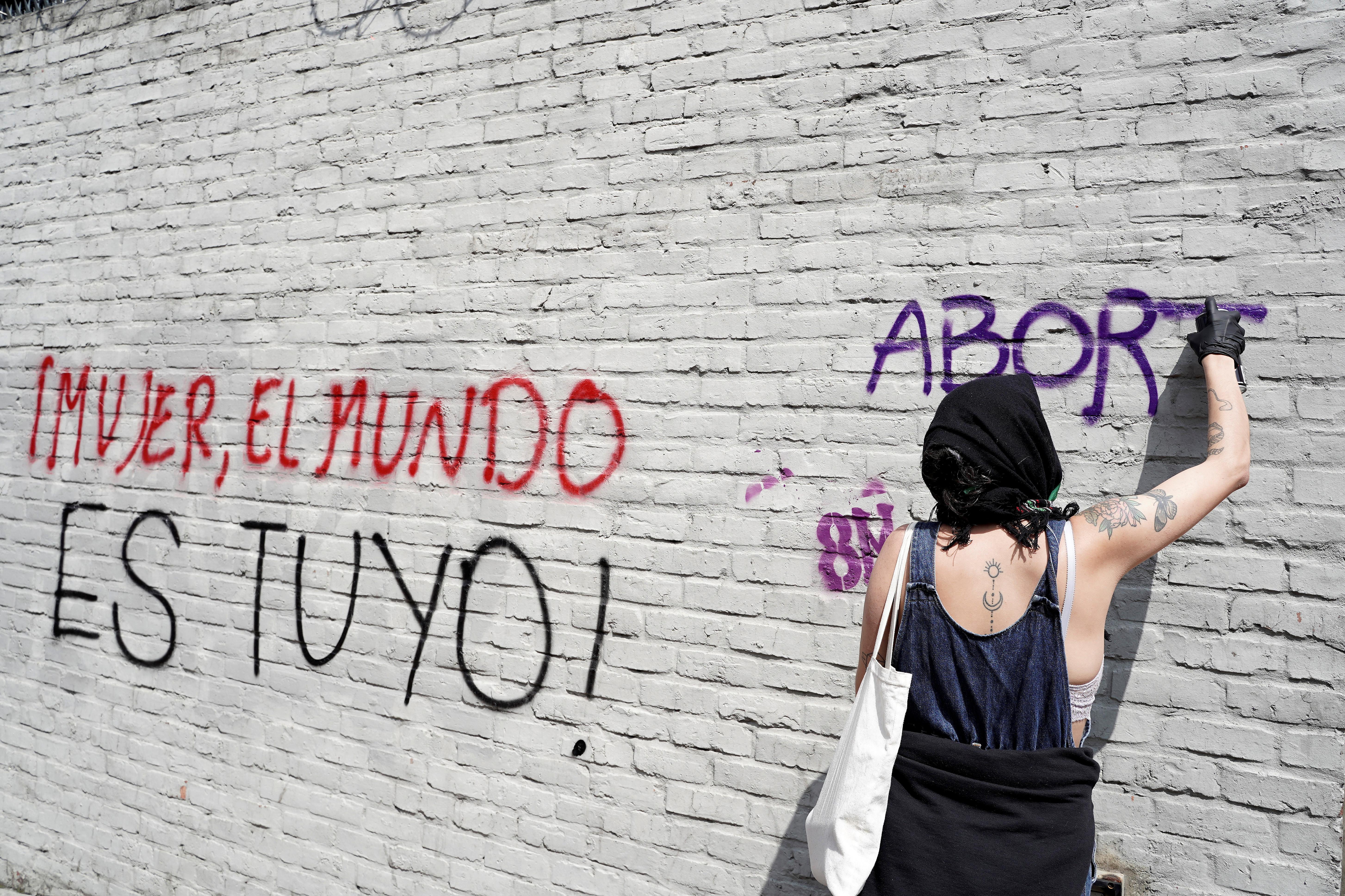 Una mujer pinta una pared con aerosol durante una marcha para conmemorar el Día Internacional de la Mujer en Bogotá, Colombia, el 8 de marzo de 2020. El graffiti dice