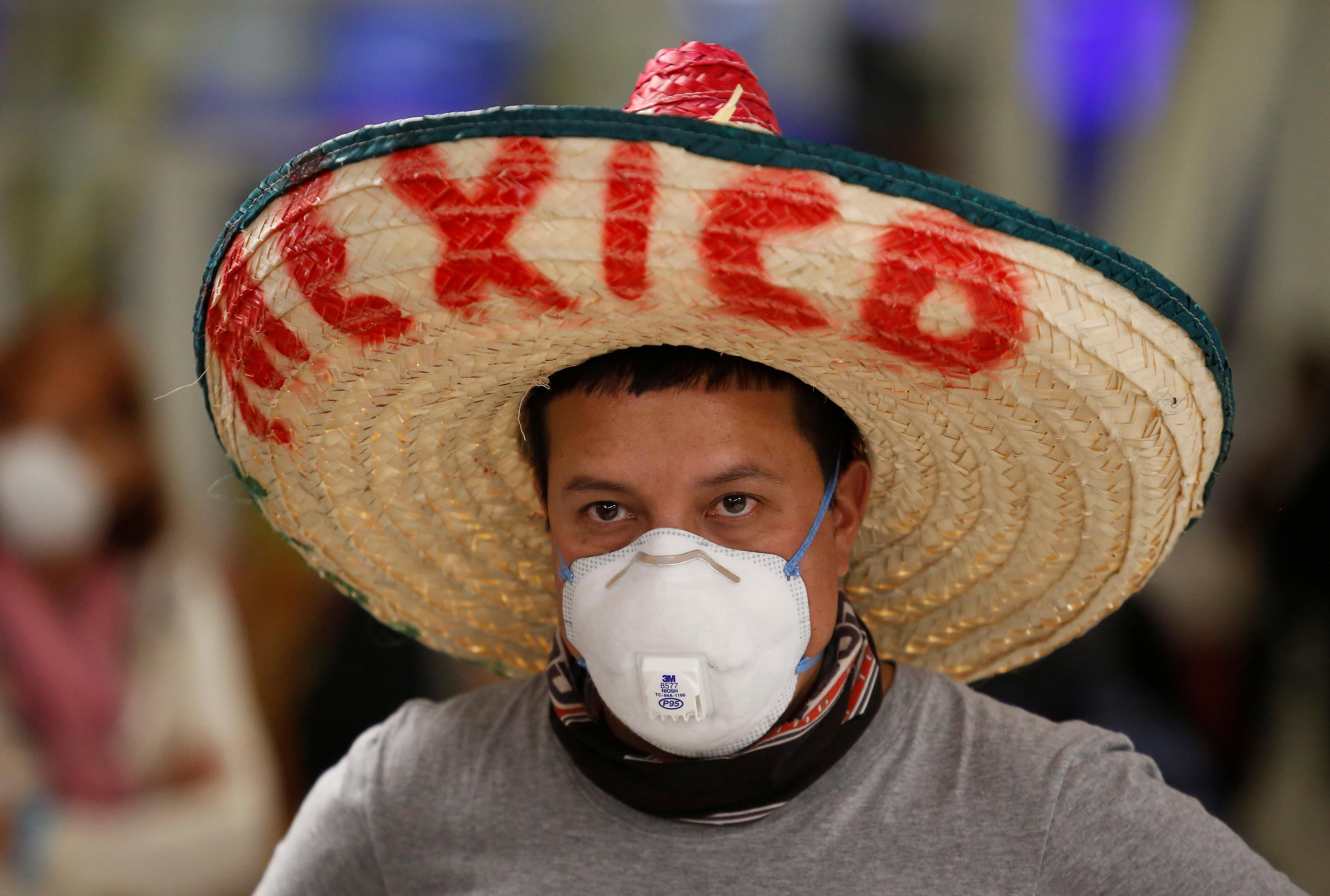 Un turista ecuatoriano varado, con una máscara facial y un sombrero tradicional mexicano, es fotografiado mientras espera un nuevo vuelo después de que el gobierno de Ecuador cerró sus fronteras debido a la propagación de la enfermedad por coronavirus (COVID-19), en el Aeropuerto Internacional Benito Juárez en Ciudad de México, México 16 de marzo de 2020.