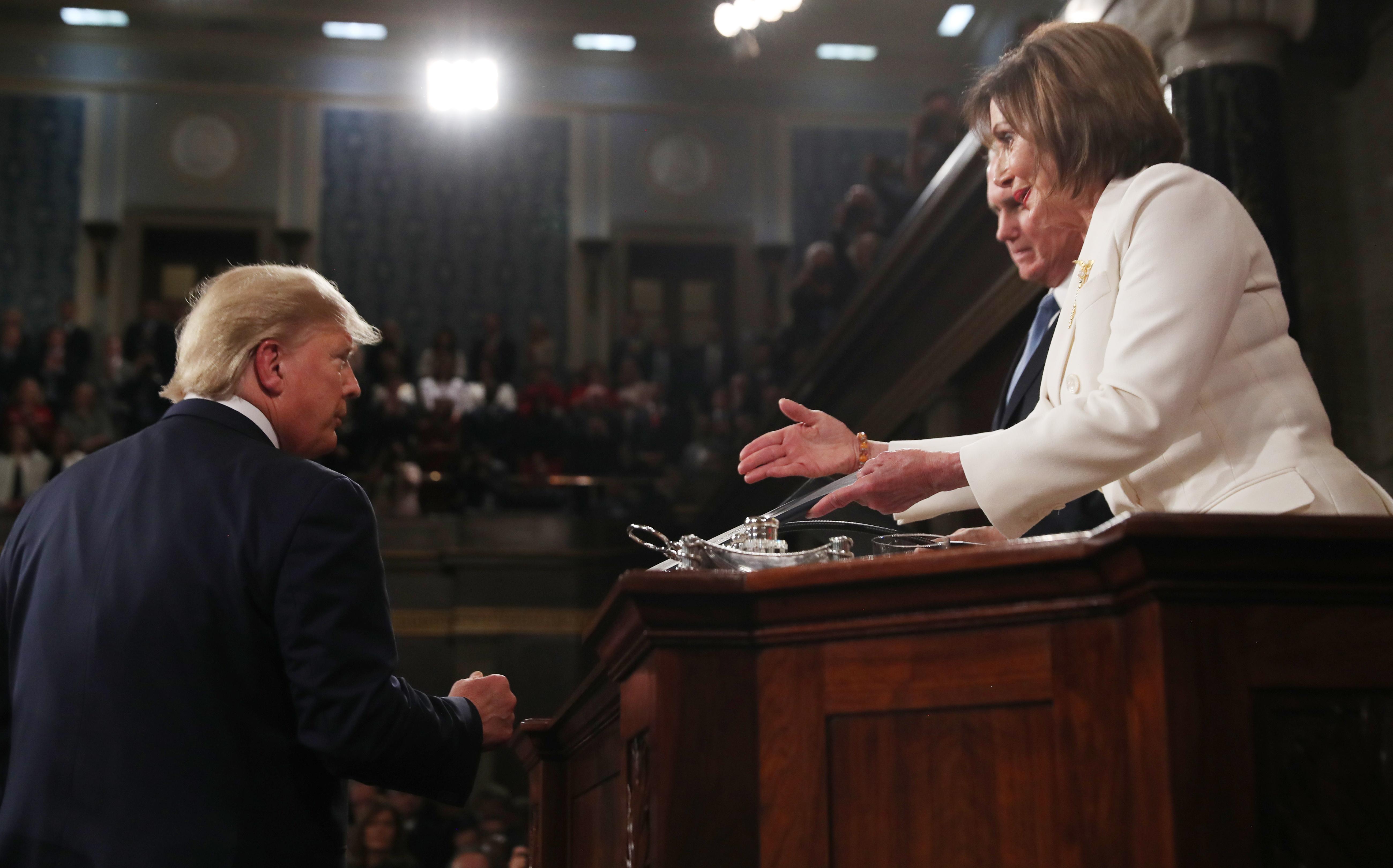 El presidente de Estados Unidos, Donald Trump, llega para ofrecer su discurso sobe el Estado de la Unión en un pleno del Congreso, en la Cámara de Representantes, en el Capitolio, en Washington, el martes 4 de febrero de 2020, mientras la presidenta de la Cámara de Representantes, Nancy Pelosi, le tiende la mano. (Leah Millis/Pool via AP)