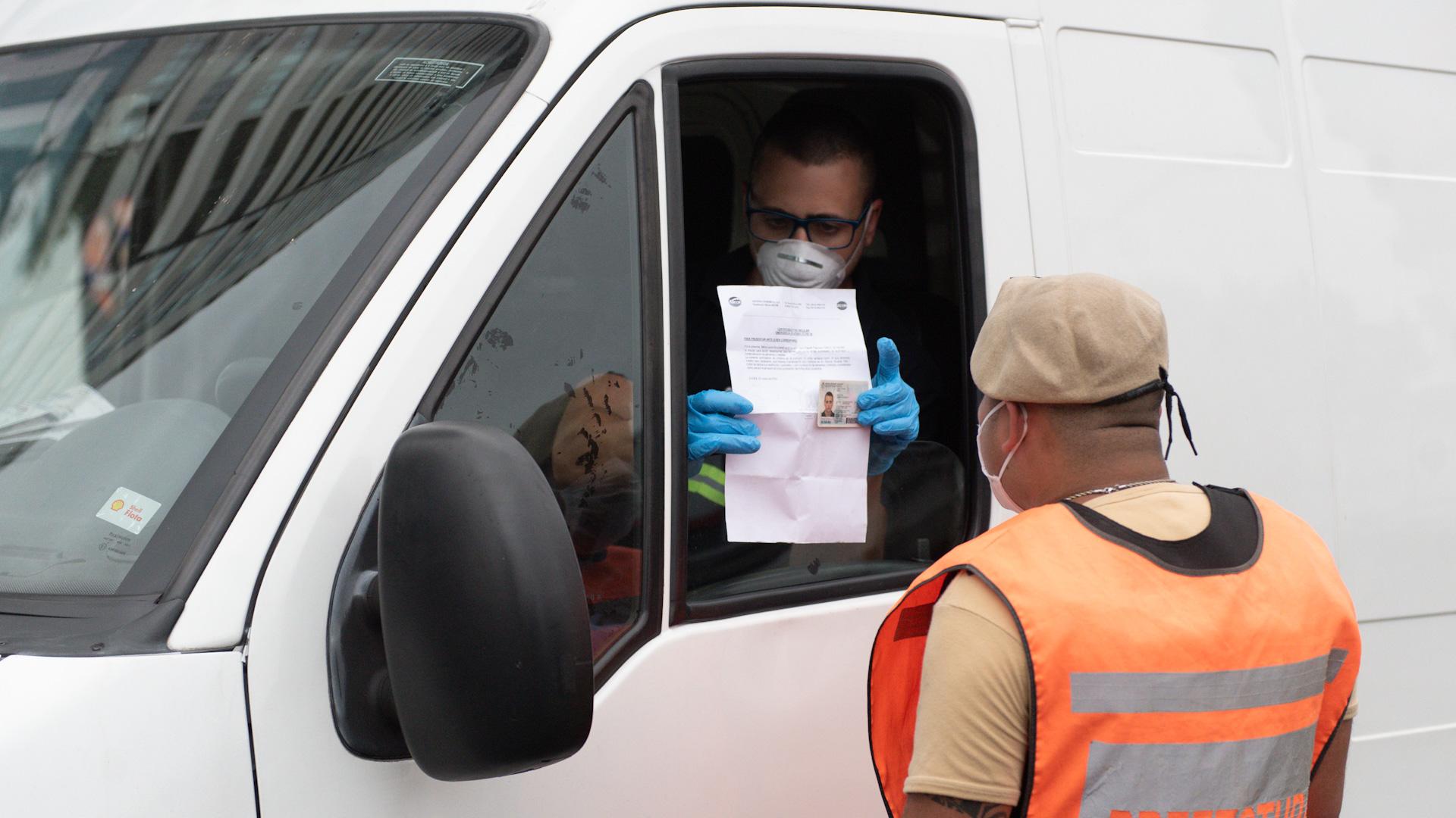 Un chofer le muestra a personal de Prefectura su permiso para circular y el documento de identidad